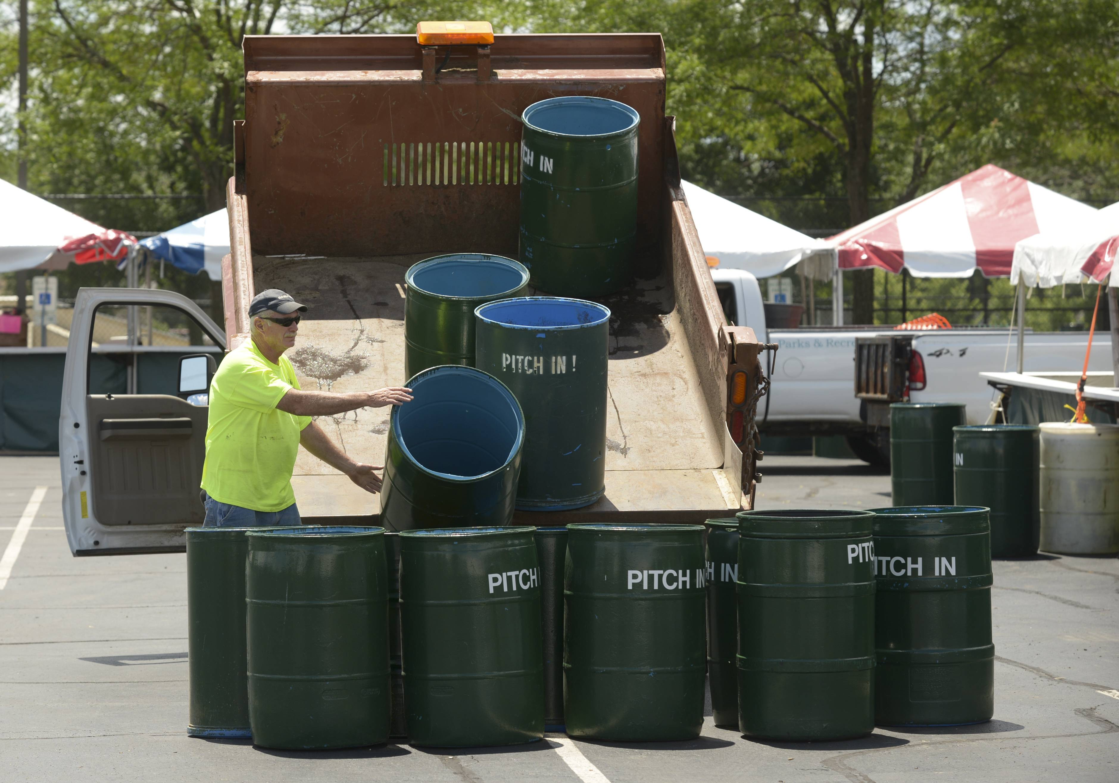 Ed Murphy of the Glendale Height Parks & Recreation Department unloads trash cans in the food court in preparation for Glendale Heights Fest in Camera Park.