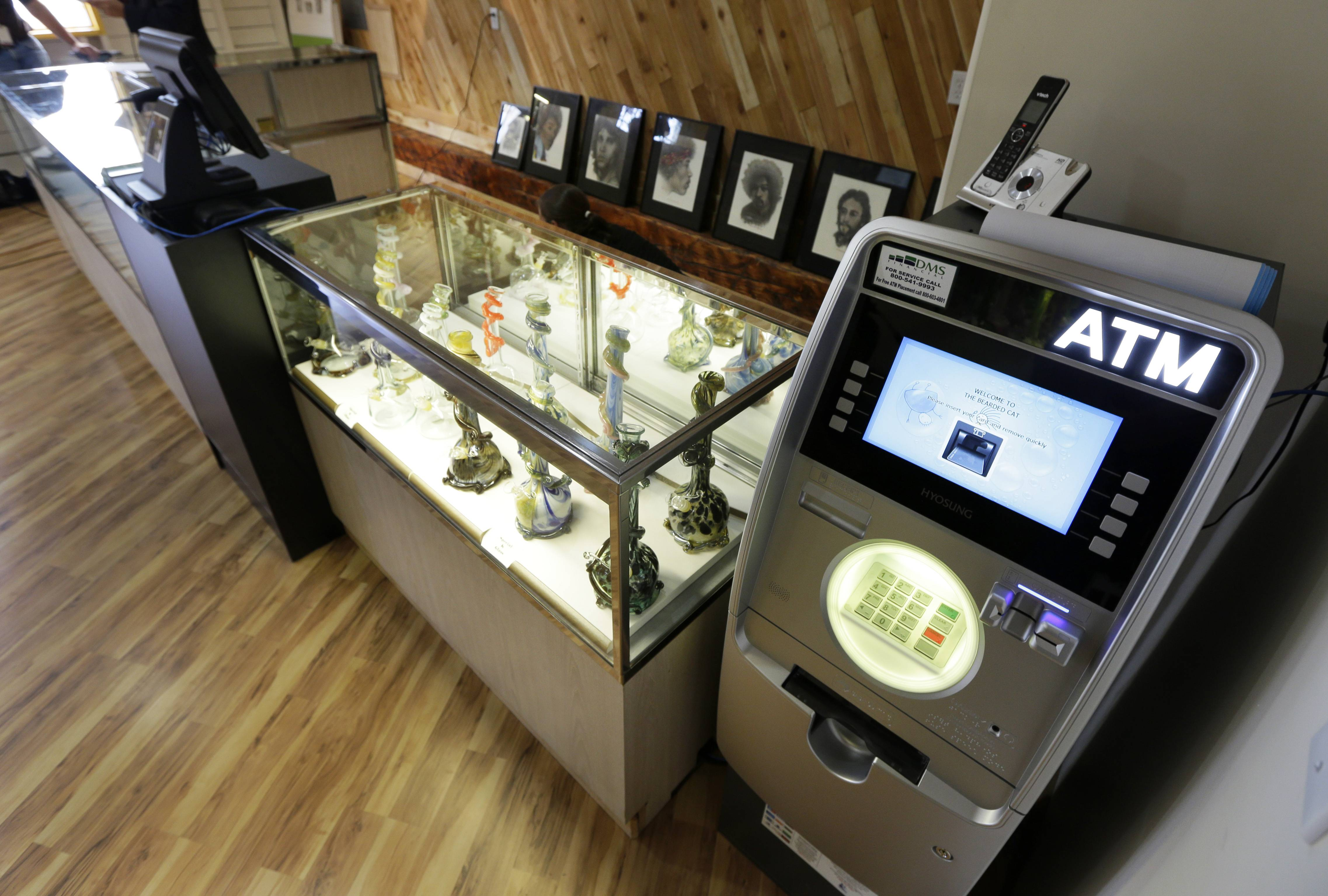 An ATM sits next to a case displaying glass bongs, Monday, July 7, 2014 at the recreational marijuana store Cannabis City in Seattle. When legal sales begin on Tuesday, July 8, 2014, the store will be the first and only store in Seattle to initially sell recreational marijuana.