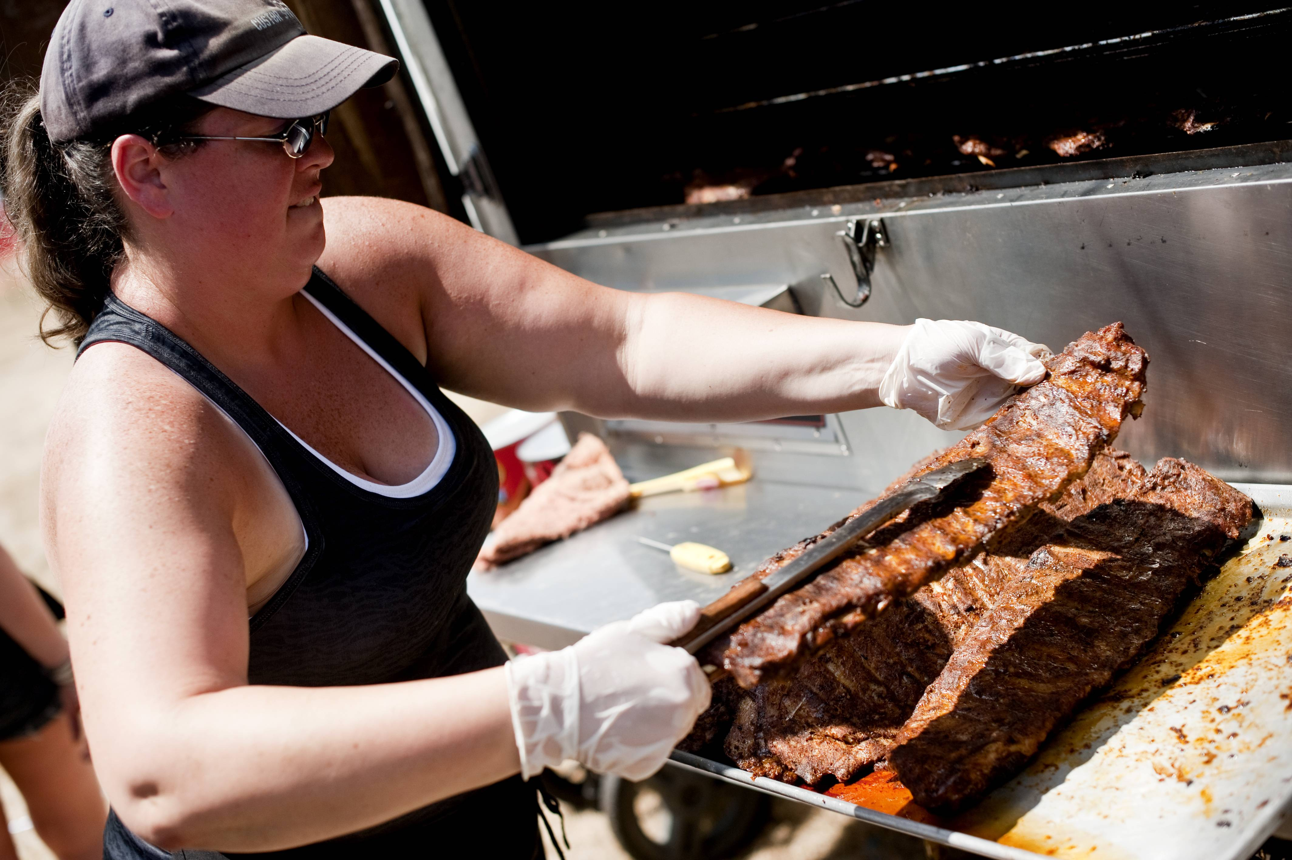 "Katie Hogan, of Bolingbrook, prepares rib slabs for Uncle Bub's BBQ at the Lake in the Hills Rockin' Ribfest Saturday in Sunset Park. Uncle Bub's participates in numerous rib fests, showcasing their ribs ""from Reno to Boston,"" says Hogan."