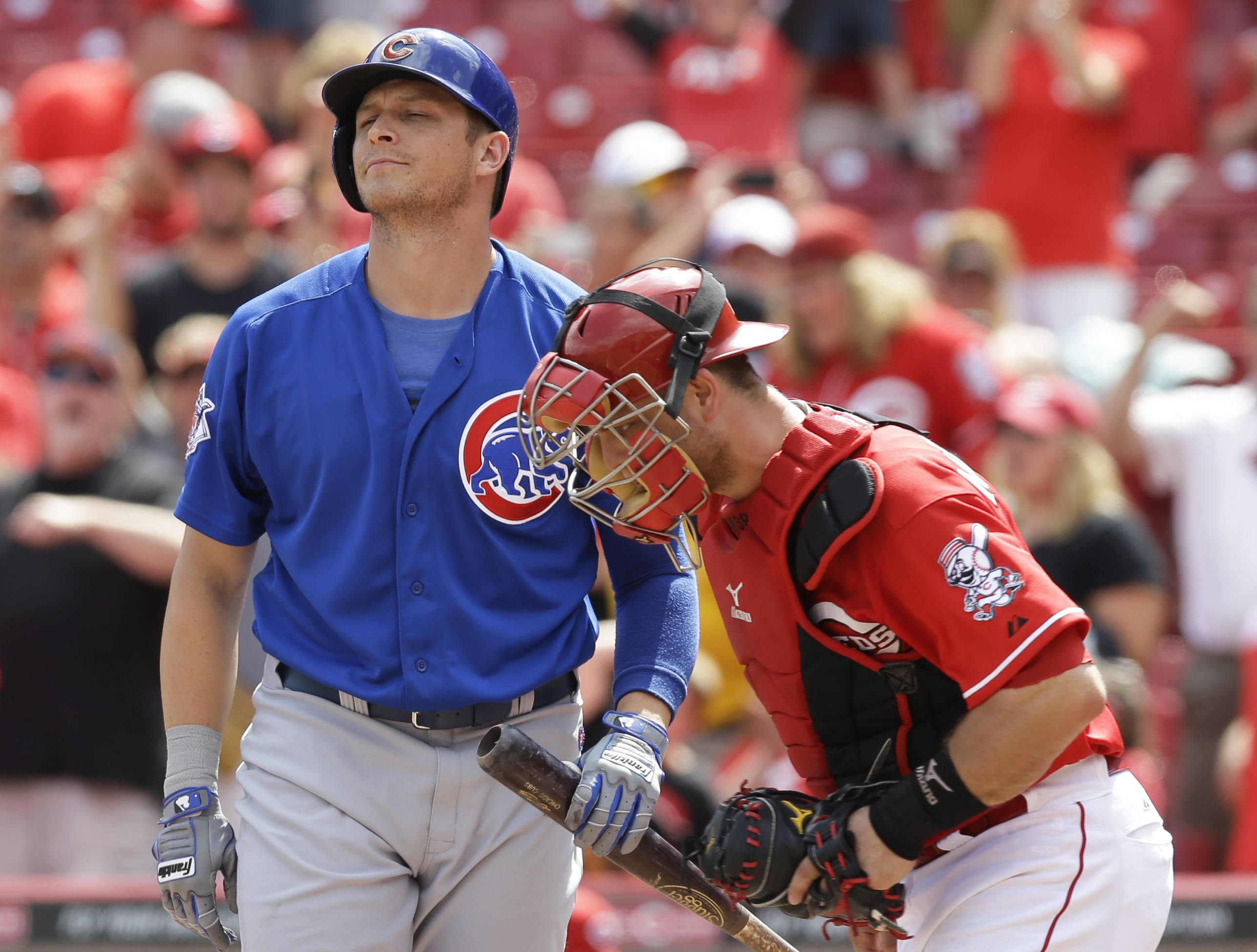Chicago Cubs' Ryan Sweeney, left, strikes out against Cincinnati Reds relief pitcher Aroldis Chapman to end a baseball game, Tuesday, July 8, 2014, in Cincinnati. Catcher Devin Mesoraco runs to the mound at right. Cincinnati won 4-2.