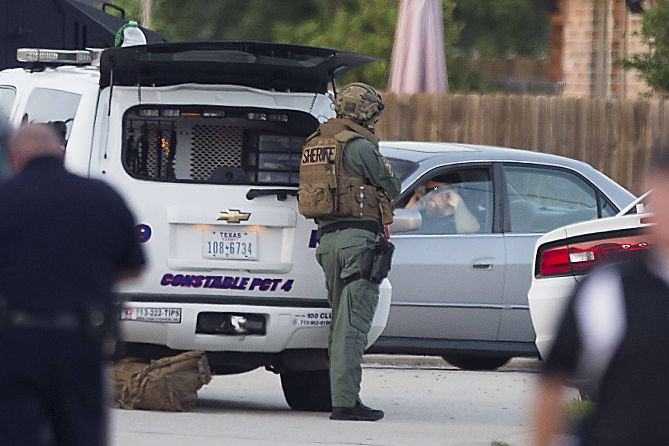 Law enforcement officers surround a shooting suspect in his car Wednesday in Spring, Texas. Deputies cornered the suspect after he is believed to have shot six people, four of them children, at another location.