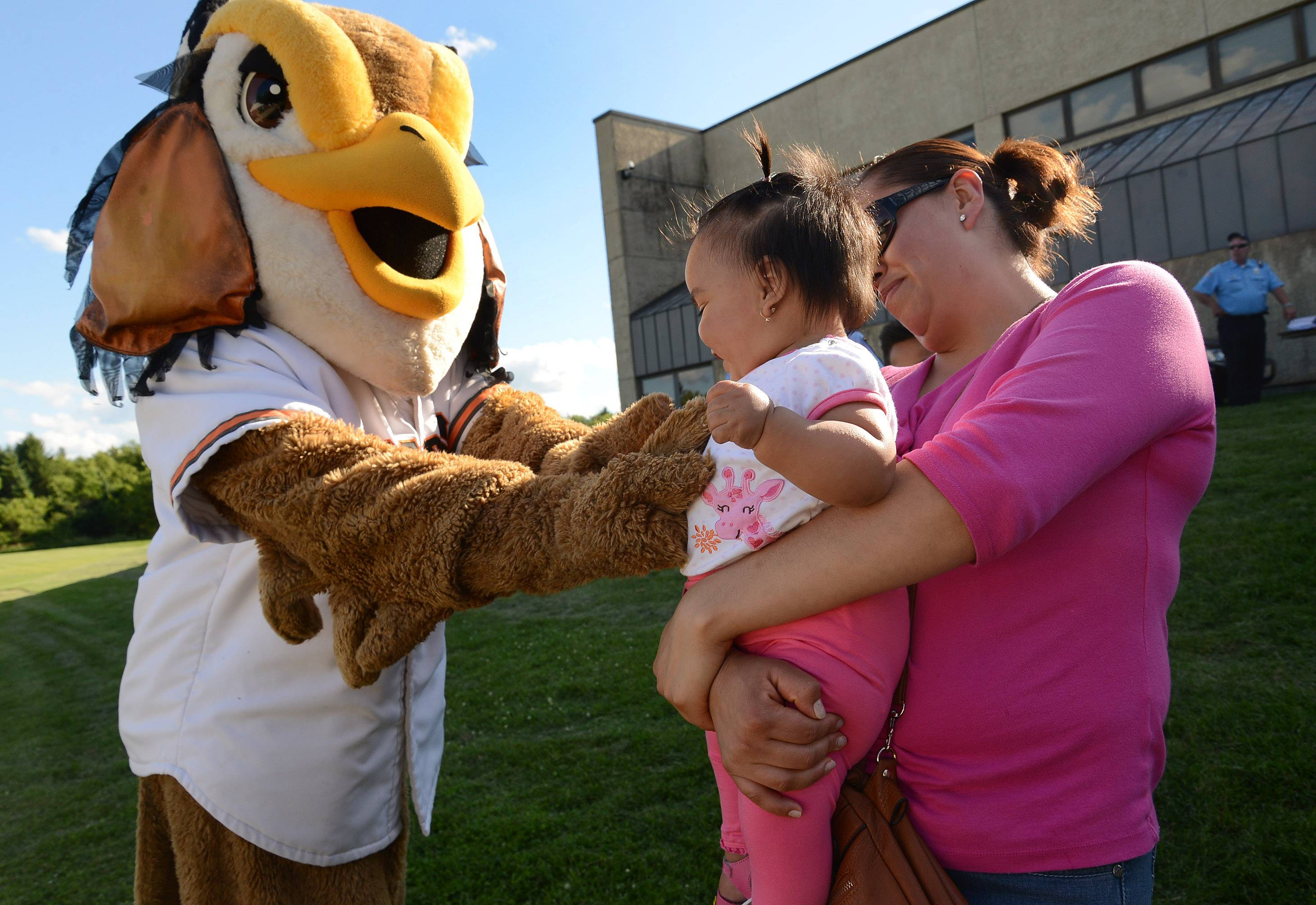 Eleven-month-old Sarai Hernandez, and her mom, Martha Medina of Hanover Park, visit with Coop, the Schaumburg Boomers mascot, on Wednesday in Hanover Park.