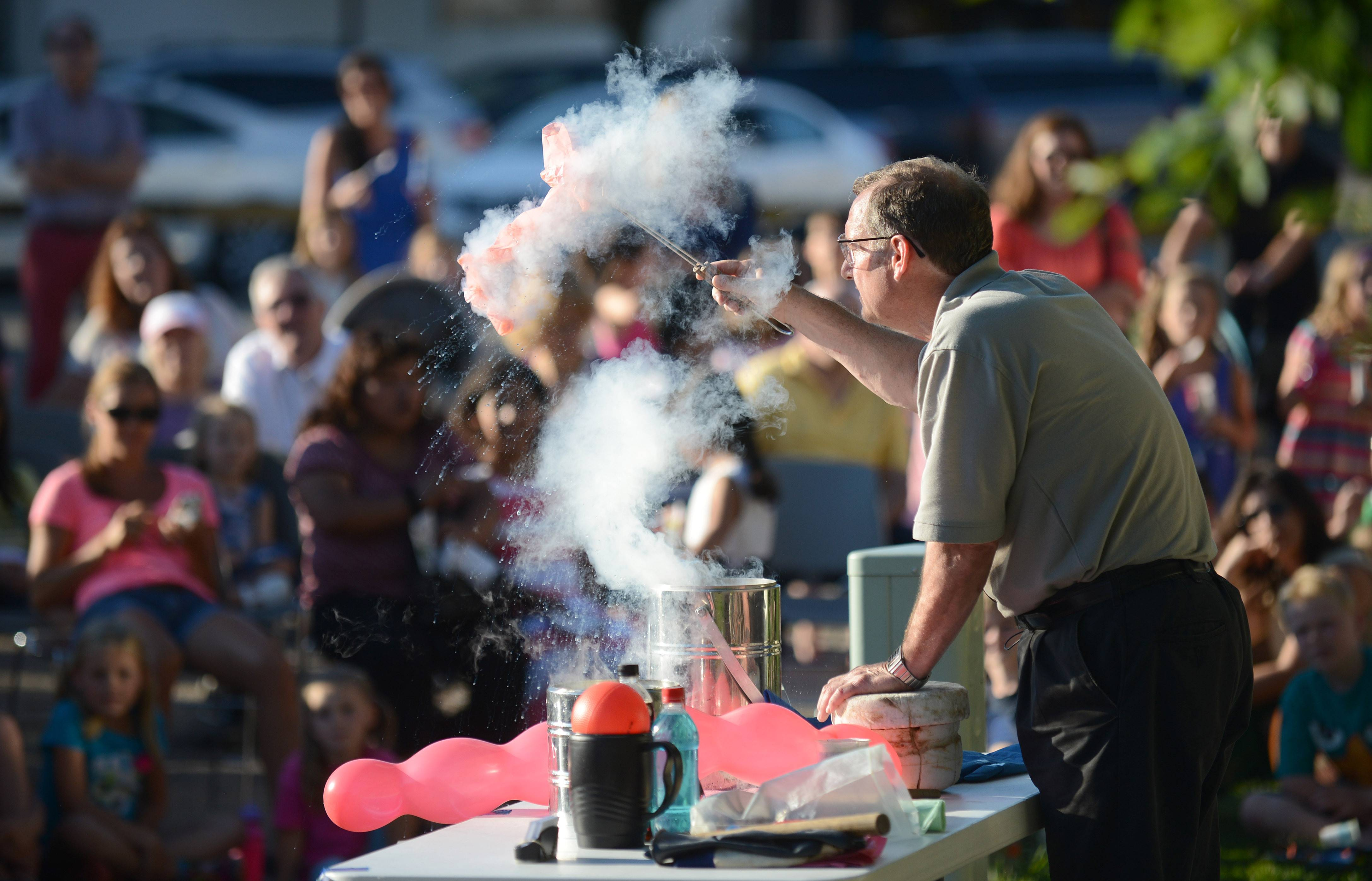 Jerry Zimmerman of Fermilab in Batavia, aka Mr. Freeze, removes balloons from liquid nitrogen during a presentation on cryogenics at Geneva Public Library's annual ice cream social on Wednesday. The balloons reinflated to full size as they warmed up. Spectators enjoyed free Dippin' Dots ice cream during the demonstration, a treat made by cryogenics.