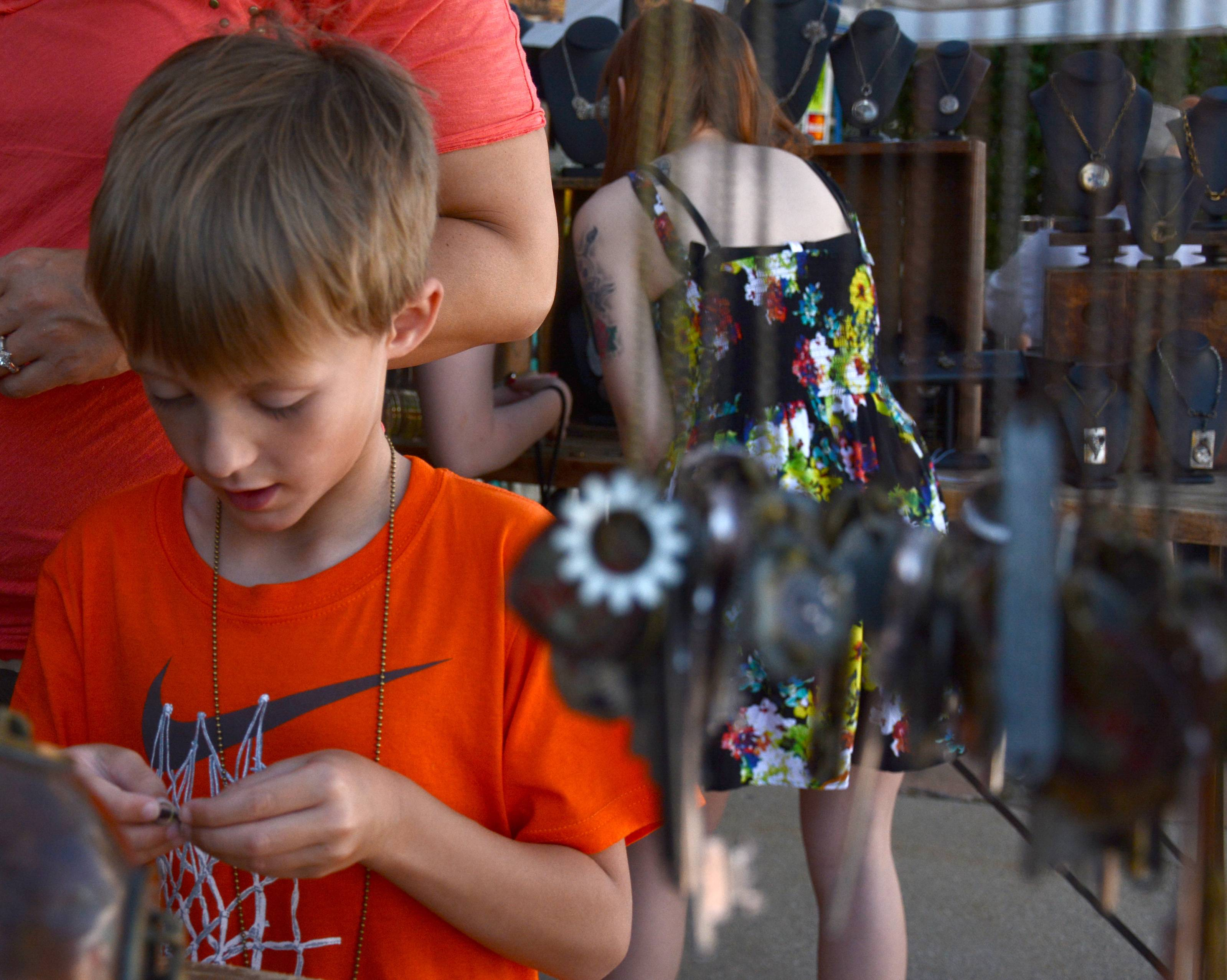Lake Finley, of Lake Forest, looks at a necklace made from old keys and clock parts at last year's festival.