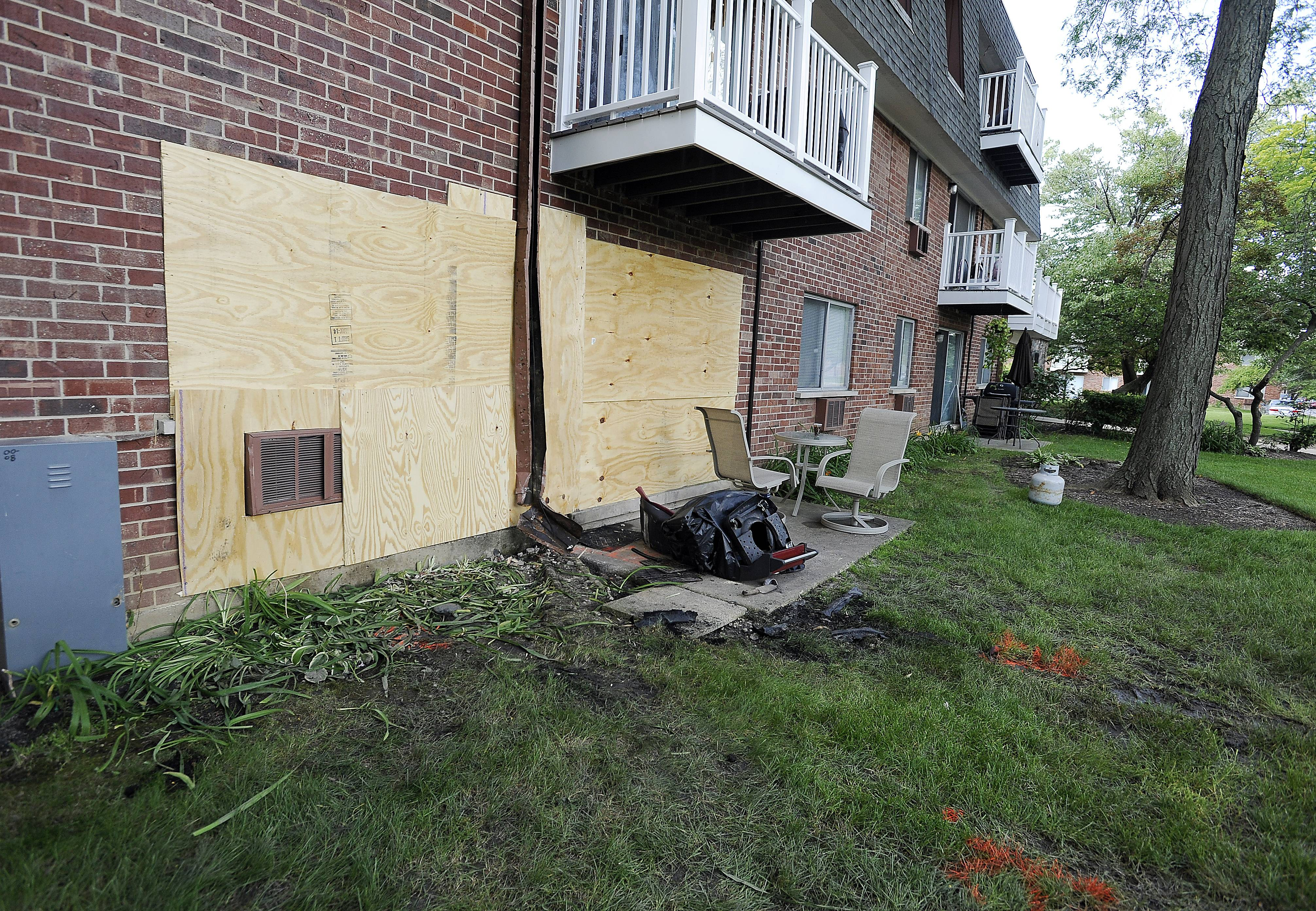 The boards show where a car struck an Elk Grove village apartment building Wednesday.
