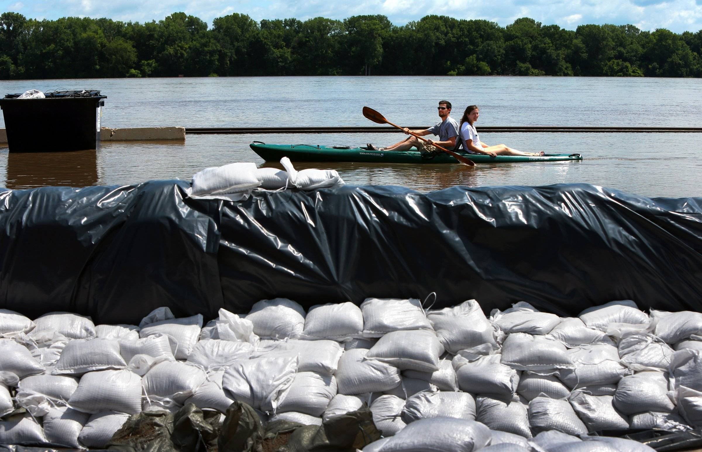 Chris Fitchett and Anne Marie Bufford pass sandbagged homes and businesses as they kayak down a flooded Front Street in Clarksville, Mo., Tuesday, July 8, 2014.