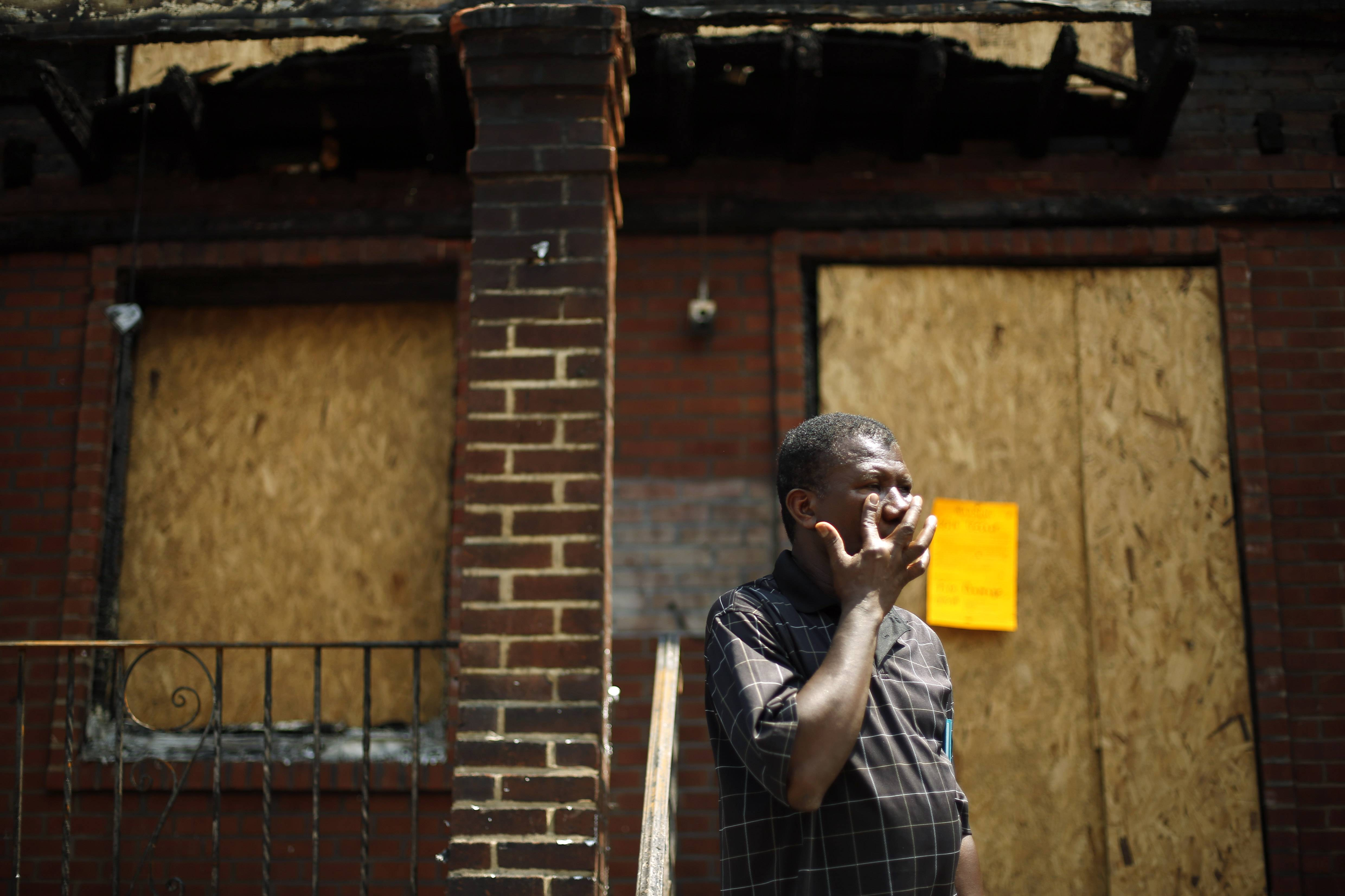 Solomon Johnson wipes his face Tuesday on the steps of his fire-damaged row house in Philadelphia, as a neighbor recounts details from the weekend fire where four young children died in a fast-moving blaze that engulfed at least 10 residences. Johnson lived next door to the children.