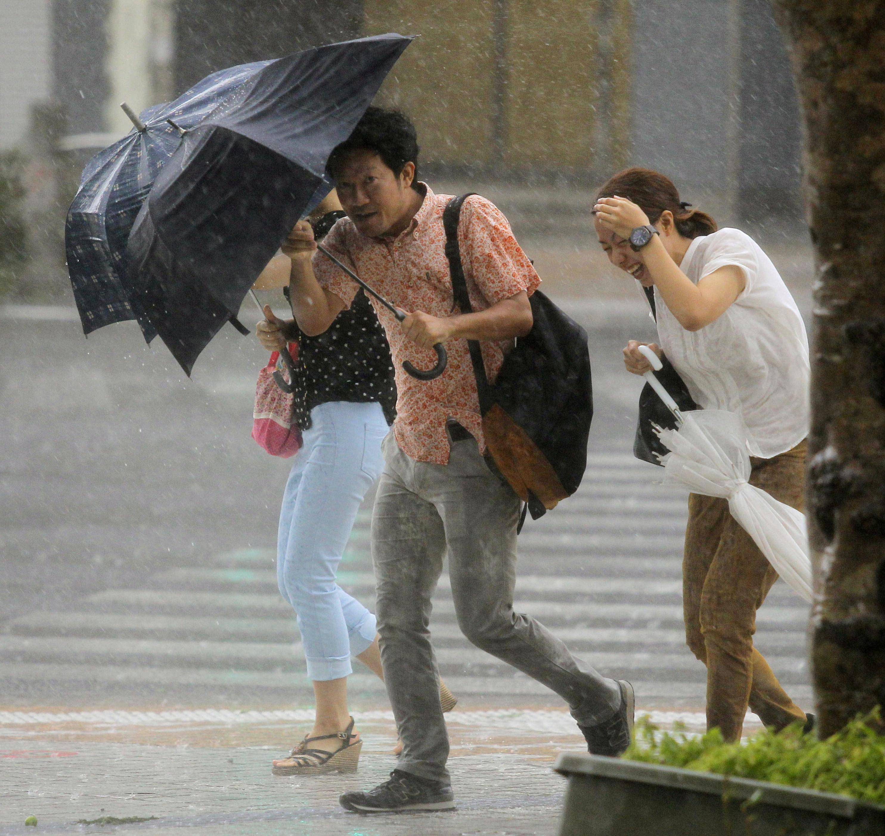 People hold umbrellas through heavy rain caused by a typhoon Wednesday in Naha, Okinawa. A powerful storm slammed through the southwestern Japanese island of Okinawa, leaving at least 28 people injured and 63,000 homes without power before swerving toward the bigger island of Kyushu on Wednesday.