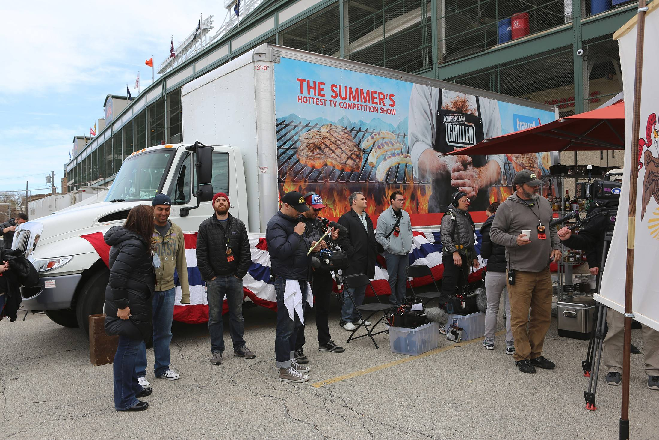 Members of the production crew for 'American Grilled' stand by a truck outside Wrigley Field in Chicago earlier this spring. The show airs Wednesdays on Travel Channel.