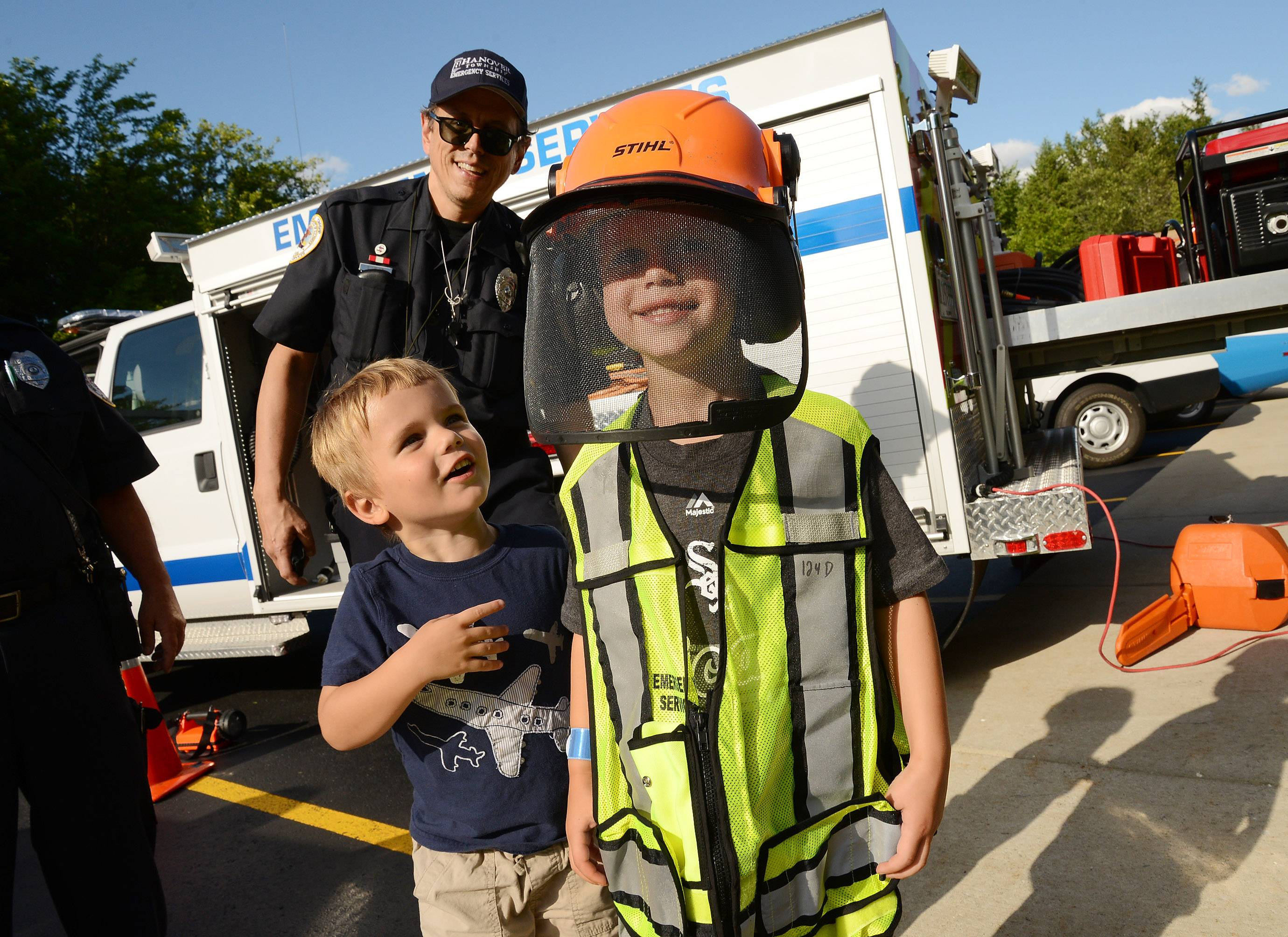 Eli Andrews, 6, right, and his brother Zeke, 3, try on some emergency equipment with the help of Hanover Township Emergency Services volunteer Edward Novit.