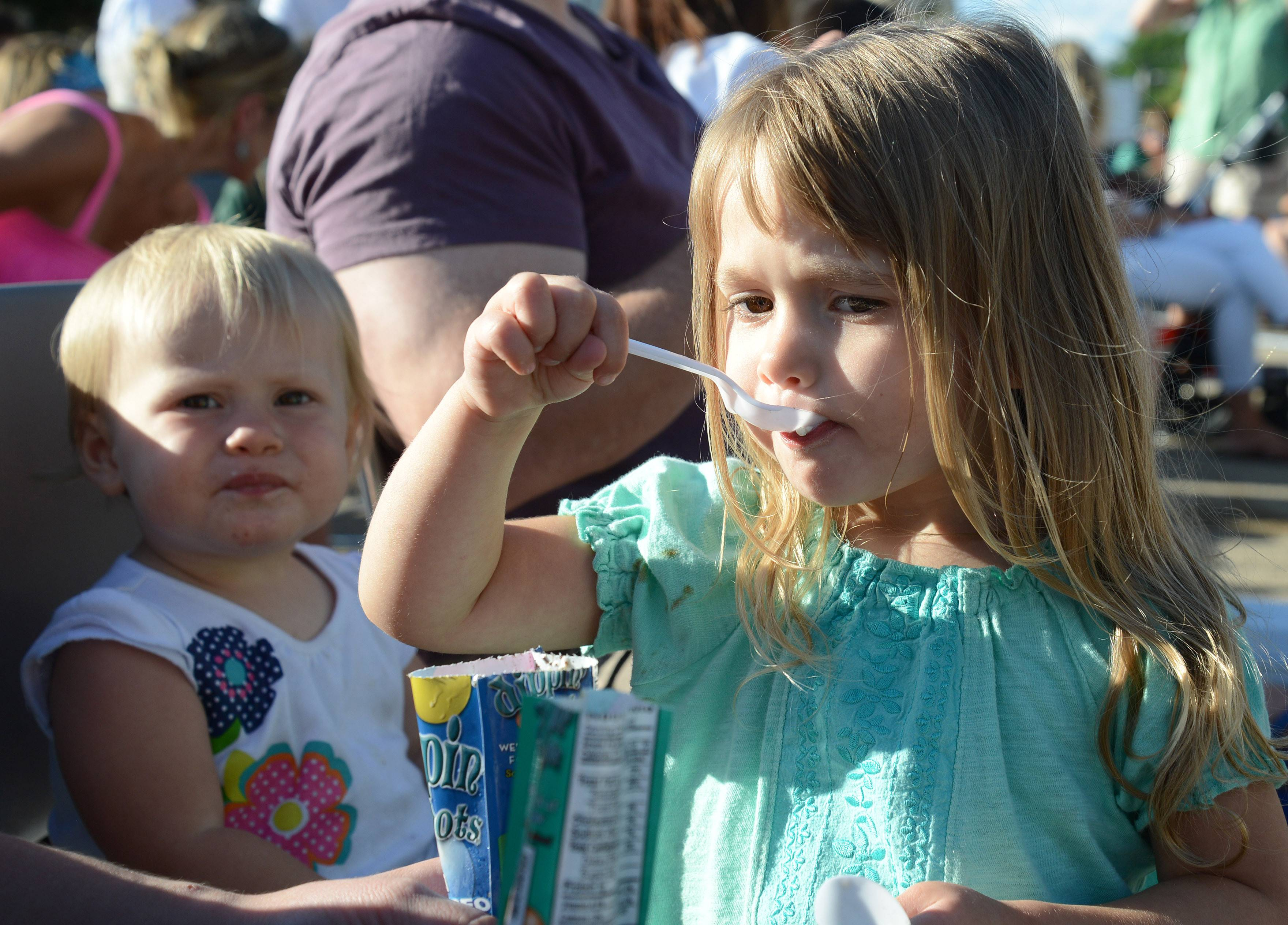 Cecilia Behrens, 3, of Geneva eats Dippin' Dots ice cream while taking turns feeding herself and little sister, Sophia, 1, at the Geneva Public Library's annual Ice Cream Social on Wednesday. This was their first time attending the event.