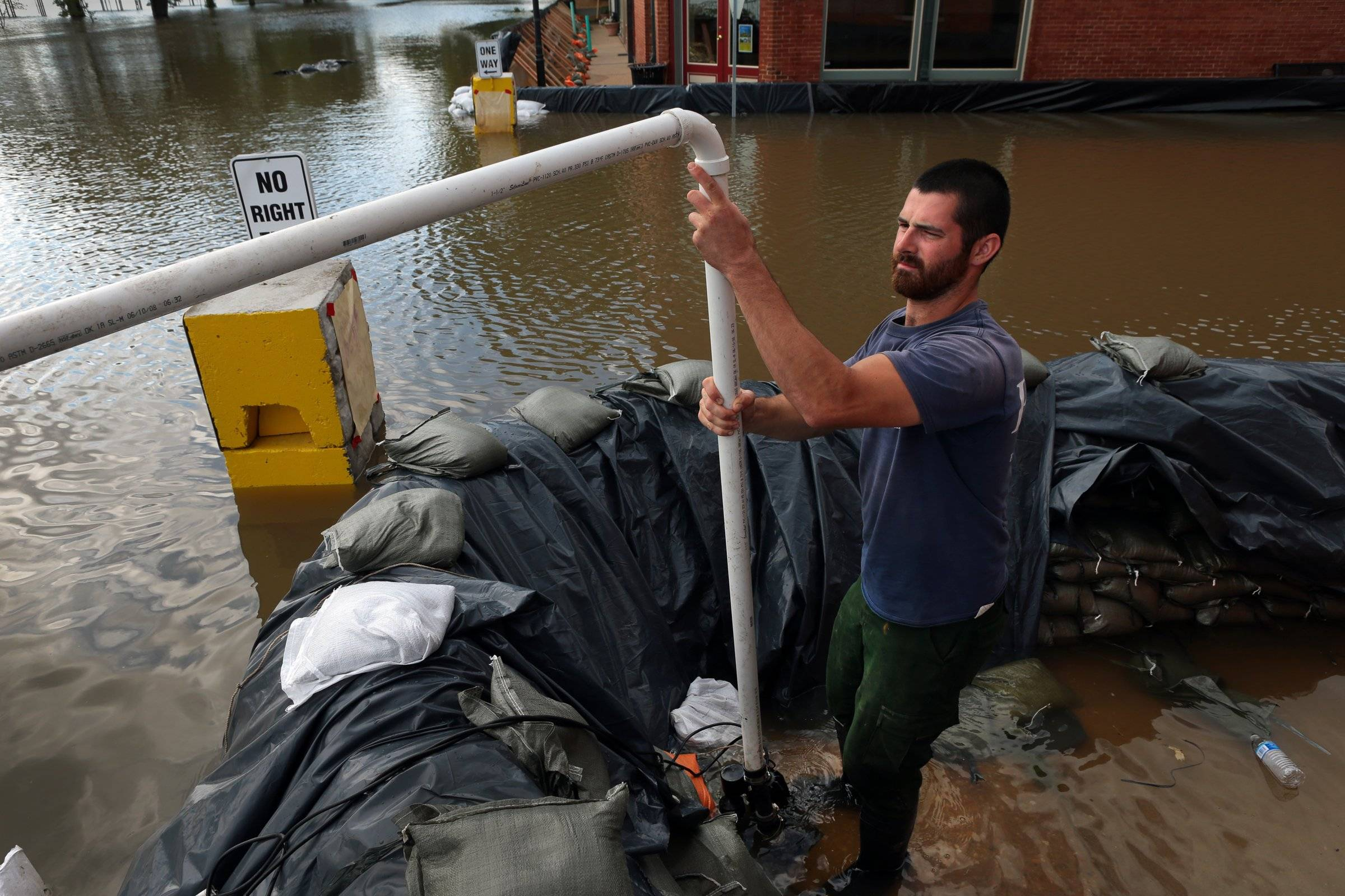 Will Burks, of AmeriCorps St. Louis, gets a sump pump ready to clear floodwater water from behind a sandbagged wall in downtown Clarksville, Mo. Tuesday, July 8, 2014.