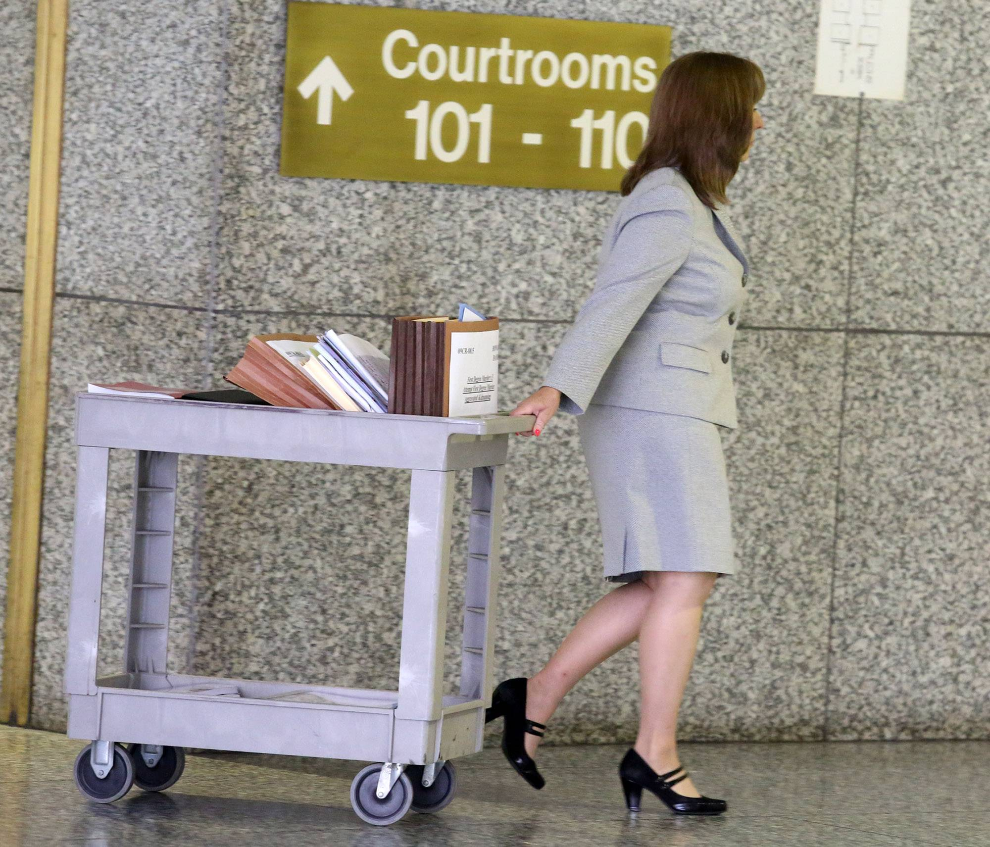 Cook County Assistant State's Attorney Maria McCarthy, lead prosecutor in the D'Andre Howard trial, pulls a case files cart to Wednesday's sentencing hearing at the Cook County courthouse in Rolling Meadows.
