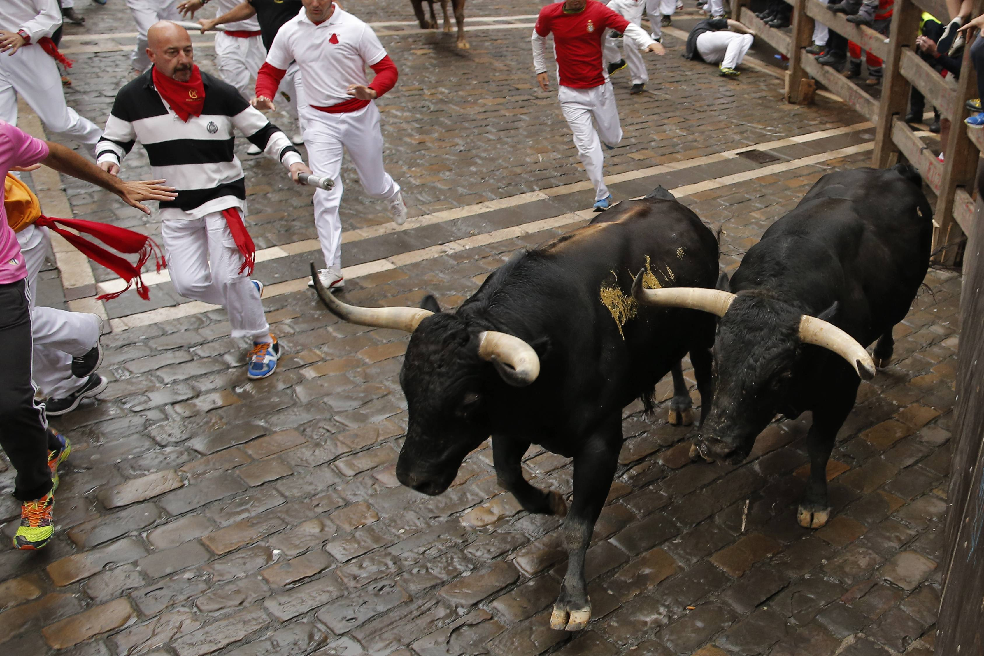 "Revelers and ""Victoriano del Rio Cortes"" fighting bulls run on Estafeta Street during the running of the bulls at the San Fermin festival, in Pamplona, Spain, Wednesday, July 9, 2014."