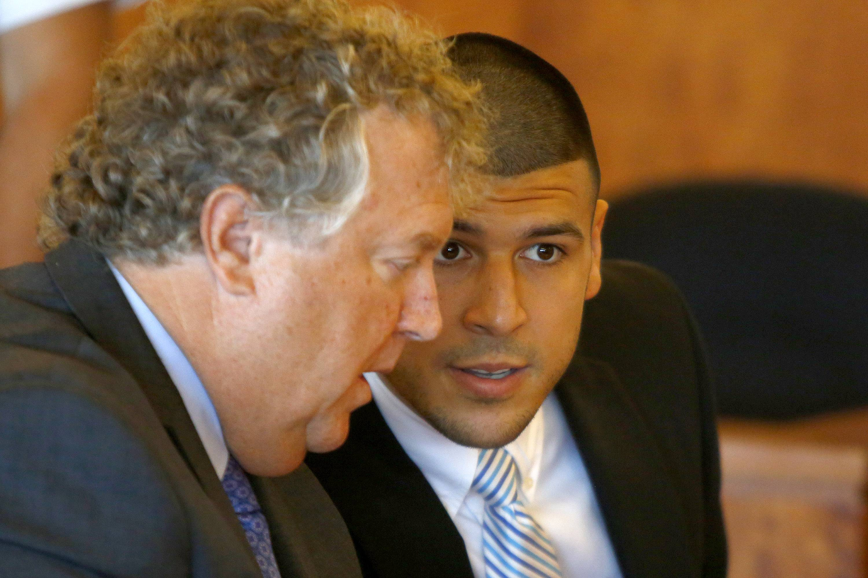 Former New England Patriots football player Aaron Hernandez, right, speaks with his lawyer Michael Fee during a hearing in Bristol County Superior Court in Fall River, Mass., Wednesday. The New England Patriots will turn over hundreds of pages of personnel records to lawyers for Hernandez but object to producing scouting reports and a psychological assessment, a team lawyer said Wednesday.