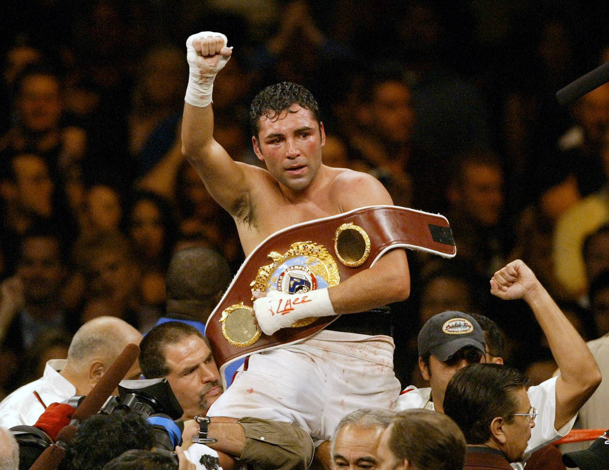 In this June 5, 2004 file photo, Oscar De La Hoya celebrates his unanimous decision victory over Germany's Felix Sturm following their WBO world middleweight title fight in Las Vegas. De La Hoya got drunk the night he won the only boxing gold for the U.S. in the 1992 Olympics, and was still drinking when he lost his last fight to Manny Pacquiao. Now sober after a second stint in rehab he's in a fight of another kind for control of his boxing company.