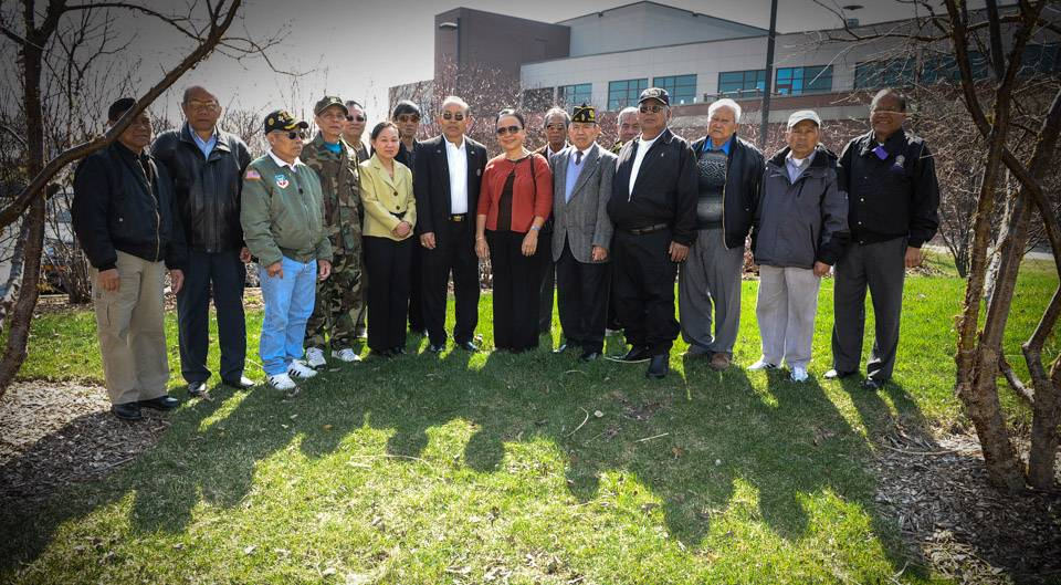 Members of the Lao-American Veterans Organization of Illinois pose by the site of their new memorial at the Elgin Veterans Memorial Park.