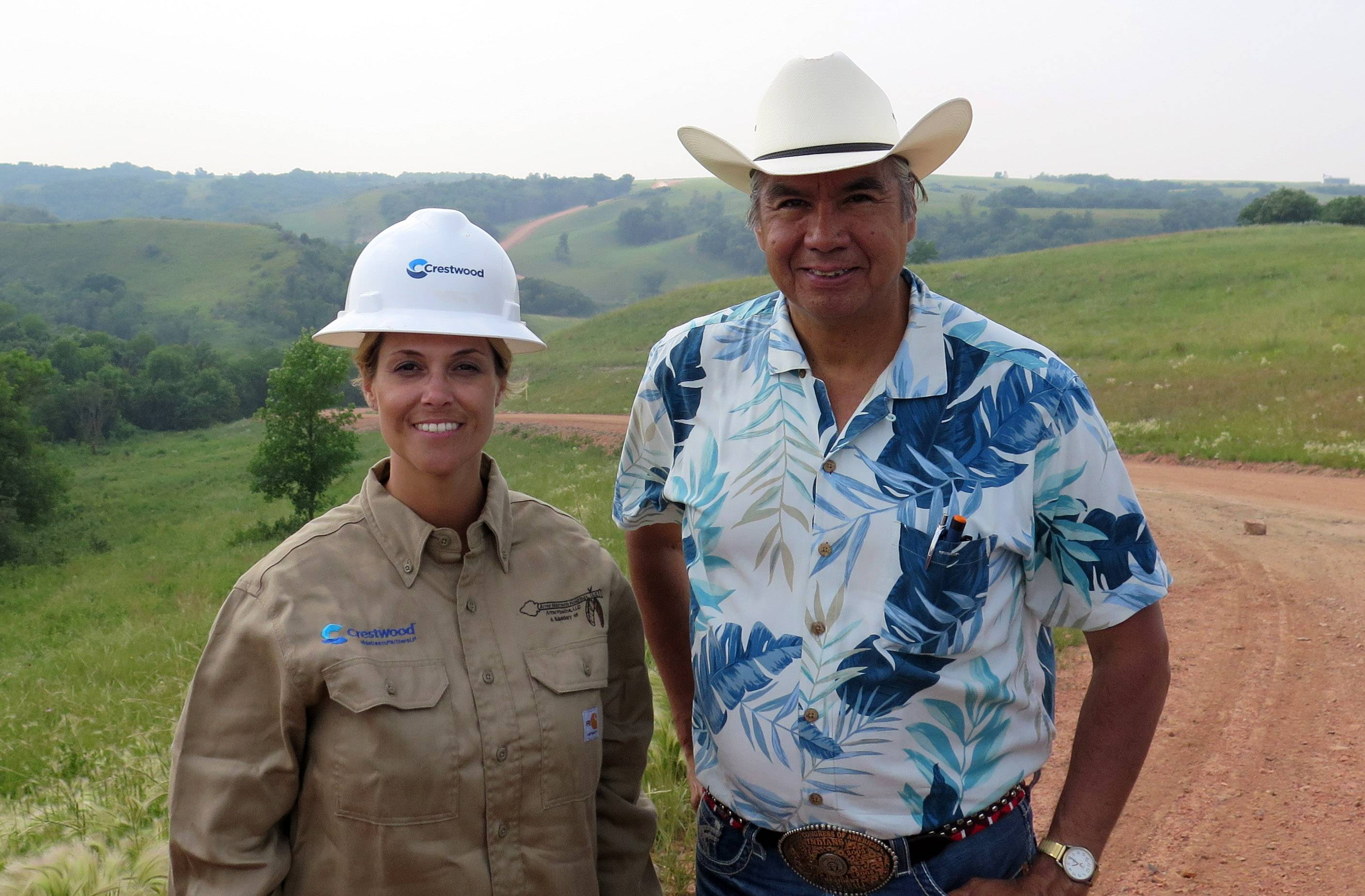 Miranda Jones, vice president of environmental safety and regulatory at Crestwood Midstream Partners, and Tex Hall, chairman of the Three Affiliated Tribes, pose for a photo near the site of a pipeline spill near Mandaree, N.D., Wednesday, July 9, 2014. A pipeline owned by a Crestwood subsidiary leaked around 1 million gallons of saltwater. Some of that liquid entered a bay that leads to a lake that is used for drinking water by the Three Affiliated Tribes.