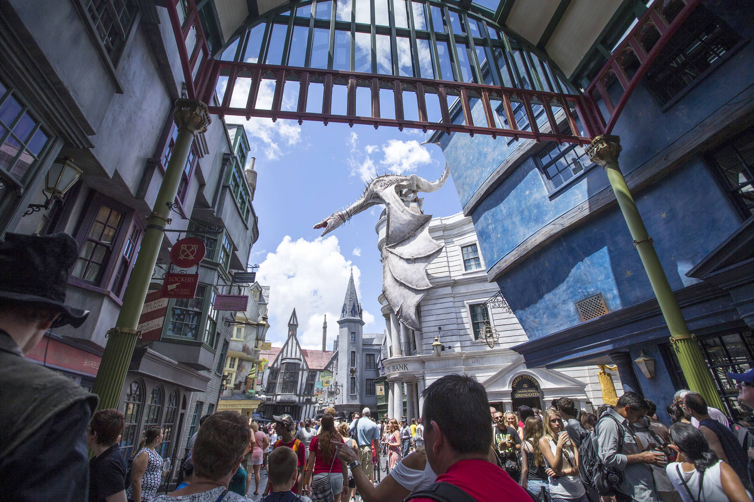 "Guests explore Diagon Alley at the Wizarding World of Harry Potter at Universal Orlando in Orlando, Fla., on Wednesday. For a second day in a row, visitors waited up to five hours to get on the ride, ""Harry Potter and the Escape from Gringotts,"" located in the new Diagon Alley section of Universal Studios."