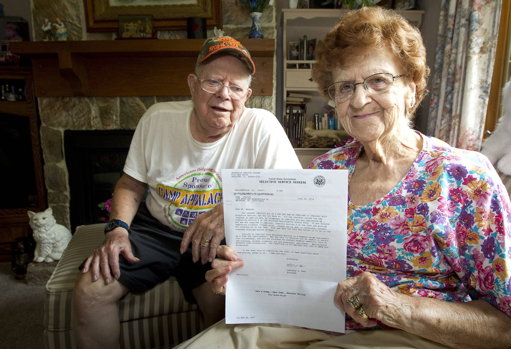 Harold Weaver sits behind his wife, Martha, who holds a letter from the Selective Service for her late father requiring him to register for the nation's military draft. The letter arrived too late for Minnick, who was born in 1894 and died in 1992.