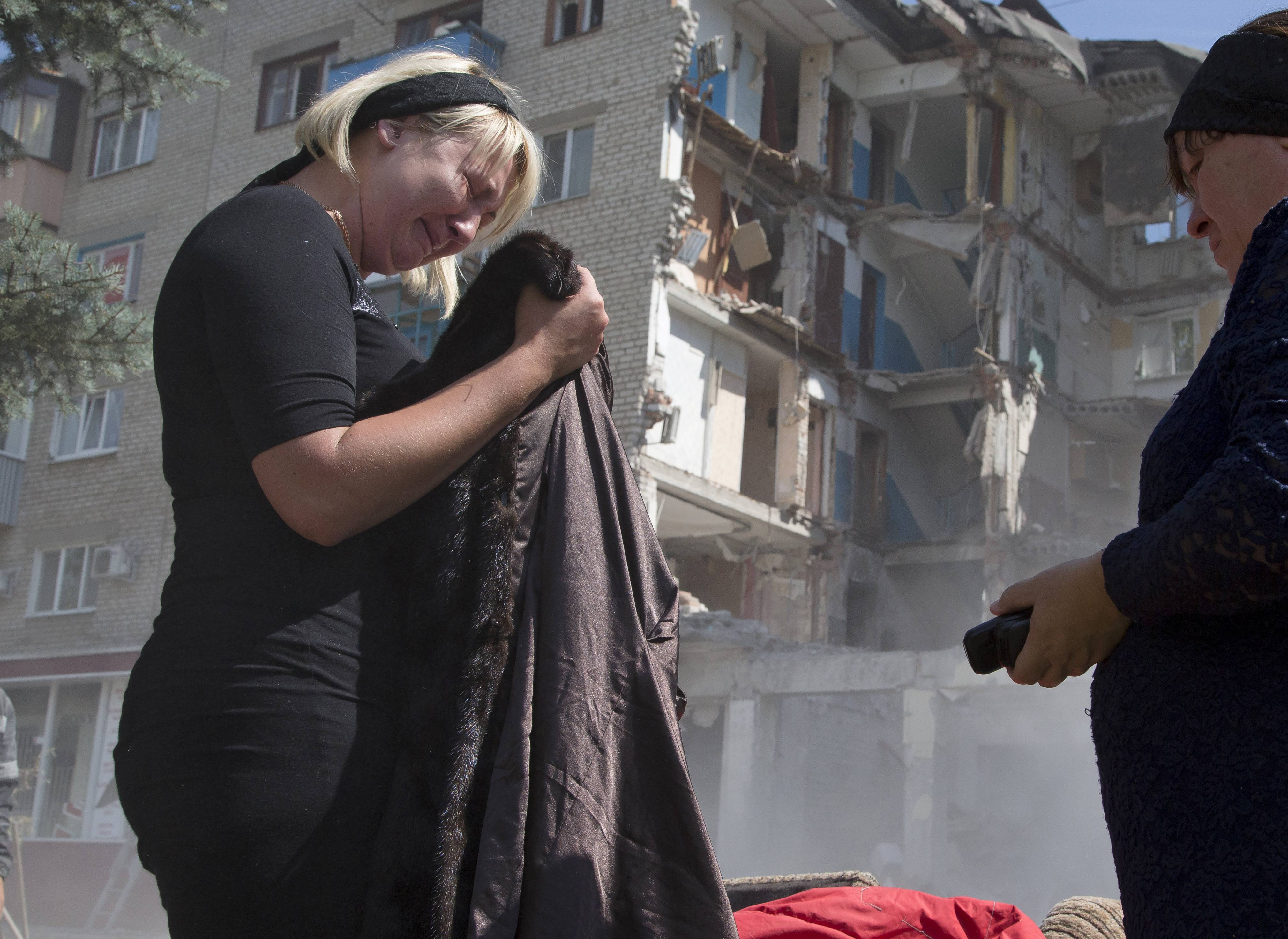 Eugenia Gubareva, left, cries after finding clothes belonging to her parents, who were killed in a building destroyed by shelling in Mikolaivka village, near the city of Slovyansk, Donetsk Region, eastern Ukraine Thursday. In the past two weeks, Ukrainian government troops have halved the amount of territory held by the rebels.
