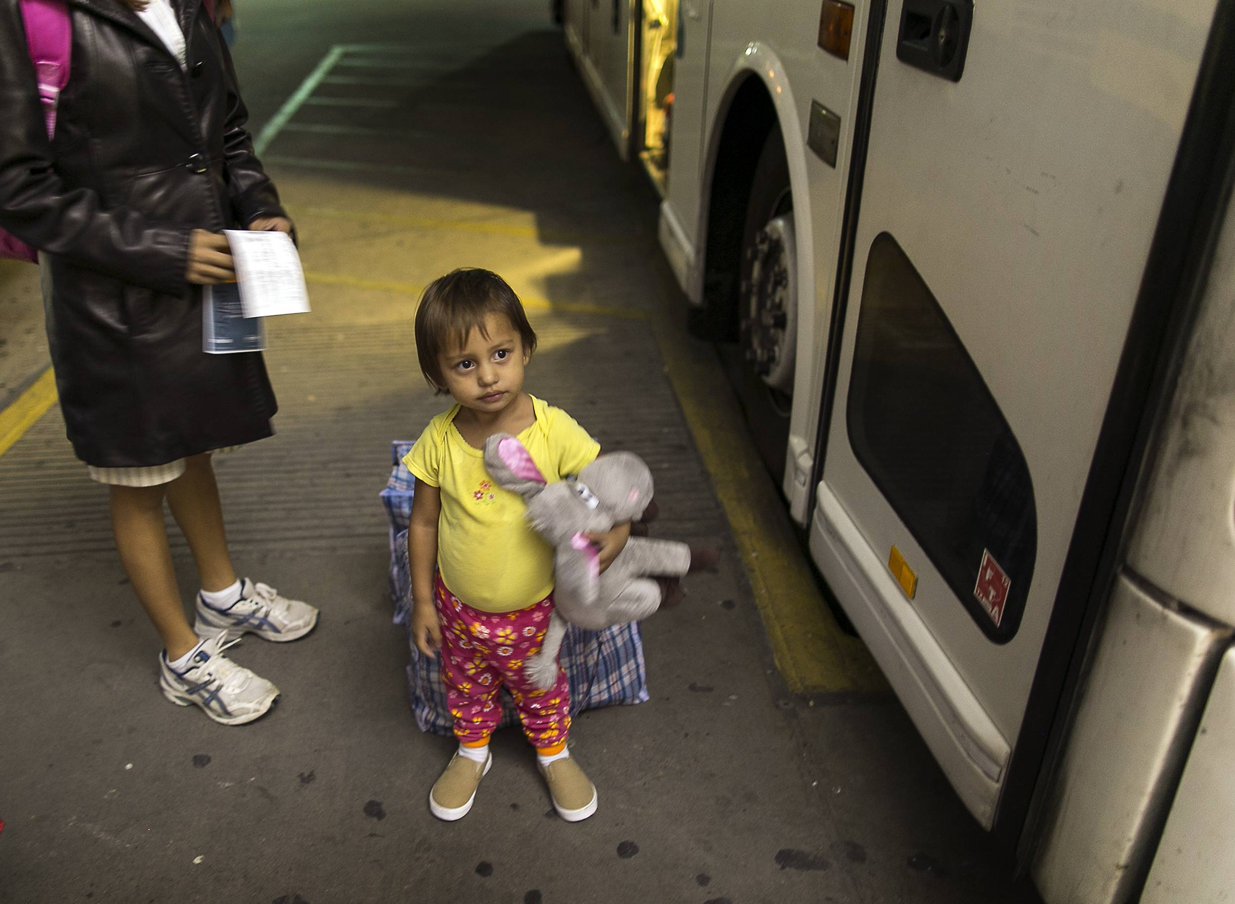 Two-year-old Adriana Ortez holds her stuffed animal, as she and her mother, Dayana Ortez, of El Salvador, wait to board a bus leaving the city bus station in McAllen, Texas, July 1. Ortez and her daughter were released on their own recognizance by U.S. Customs and Border Protection Services after entering the illegally into the U.S. from Mexico. The mother and daughter were heading to Los Angles to reunite with family.