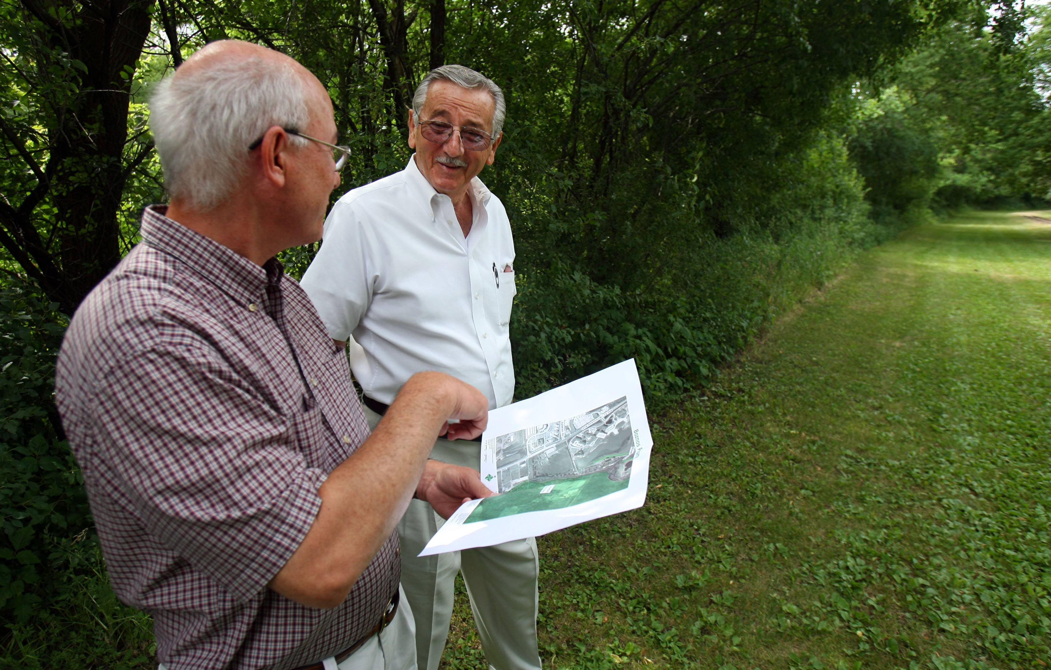 Tom Hahn, then executive director of the Lake County Forest Preserve District, left, and land owner Gus Boznos stand on the 1,500-foot stretch near Lincolnshire that will close the last gap in 31-mile Des Plaines River Trail.