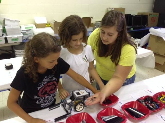 Denise Karabowicz, right, assists Elise Aponte and Brigid Mrenna with their project at the Legos Robotics Summer Camp.