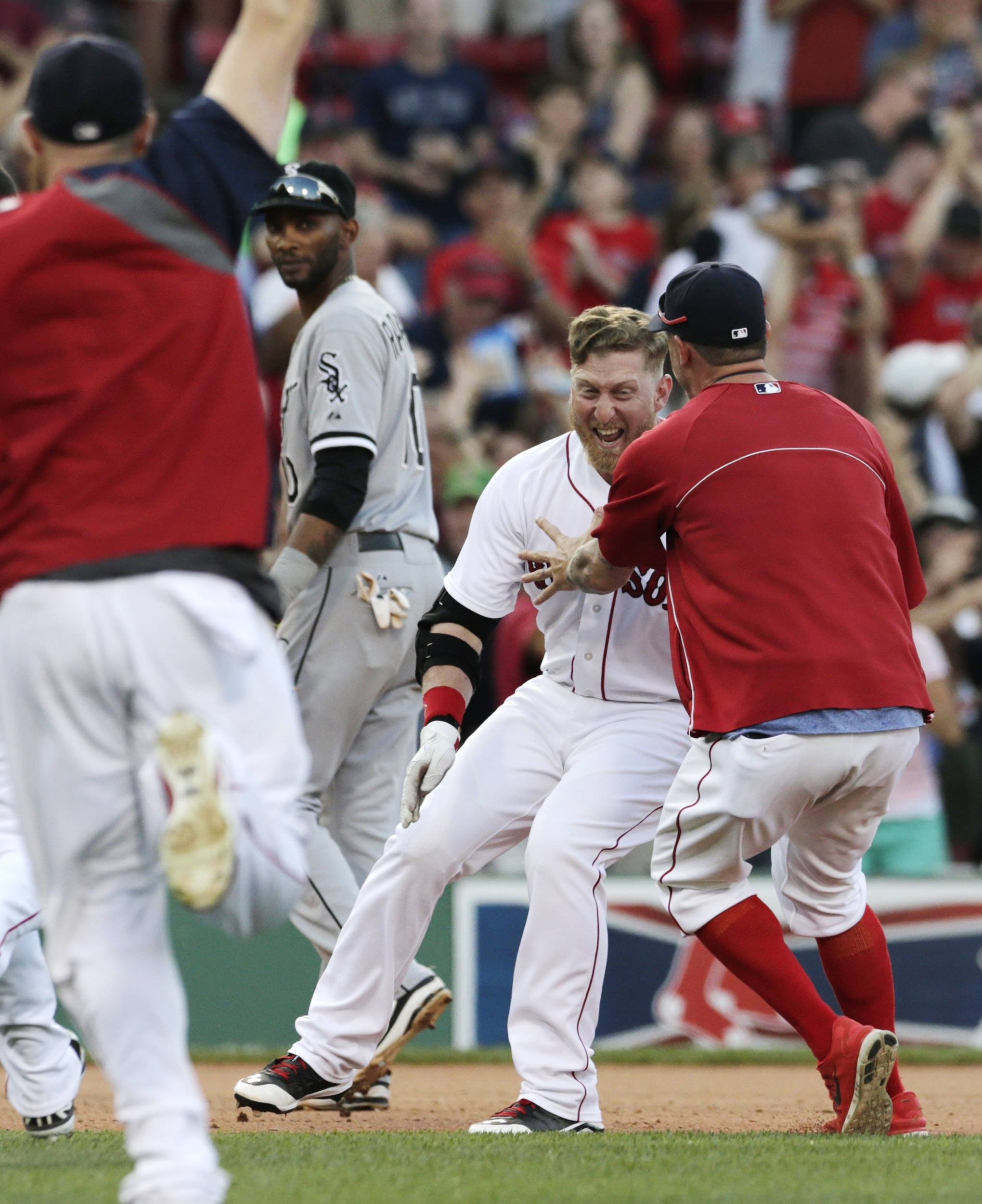 As Alexei Ramirez watches, Boston Red Sox pinch hitter Mike Carp, center is congratulated by teammates after his walk-off RBI single, breaking a 3-3 tie, against the White Sox. The Red Sox defeated the White Sox 4-3 in 10 innings.