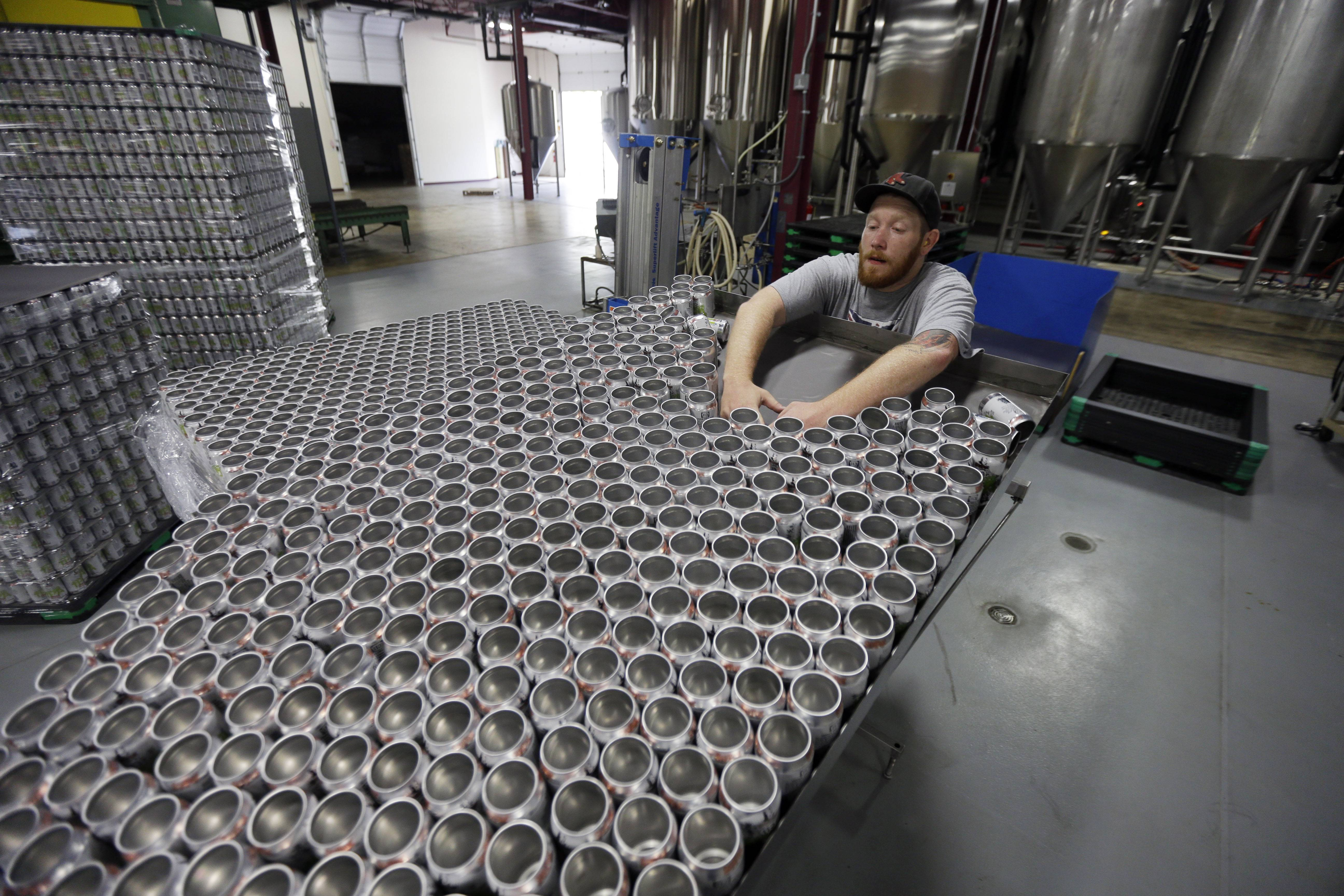 A worker loads empty cans onto the assembly line the Sly Fox Brewing Company in Pottstown, Pa. U.S. wholesale stockpiles rose in May at the weakest pace in five months as companies kept their supplies in line with slower sales.  Wholesale stockpiles grew 0.5 percent in May,
