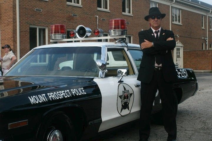 Now-retired Mount Prospect police spokesman Bill Roscop poses in 2010 with the department's 1974 Dodge Monaco, renovated to look like the Bluesmobile. When Elwood picks up a freshly paroled Jake in the movie, Elwood says he got the Bluesmobile from a Mount Prospect police auction.