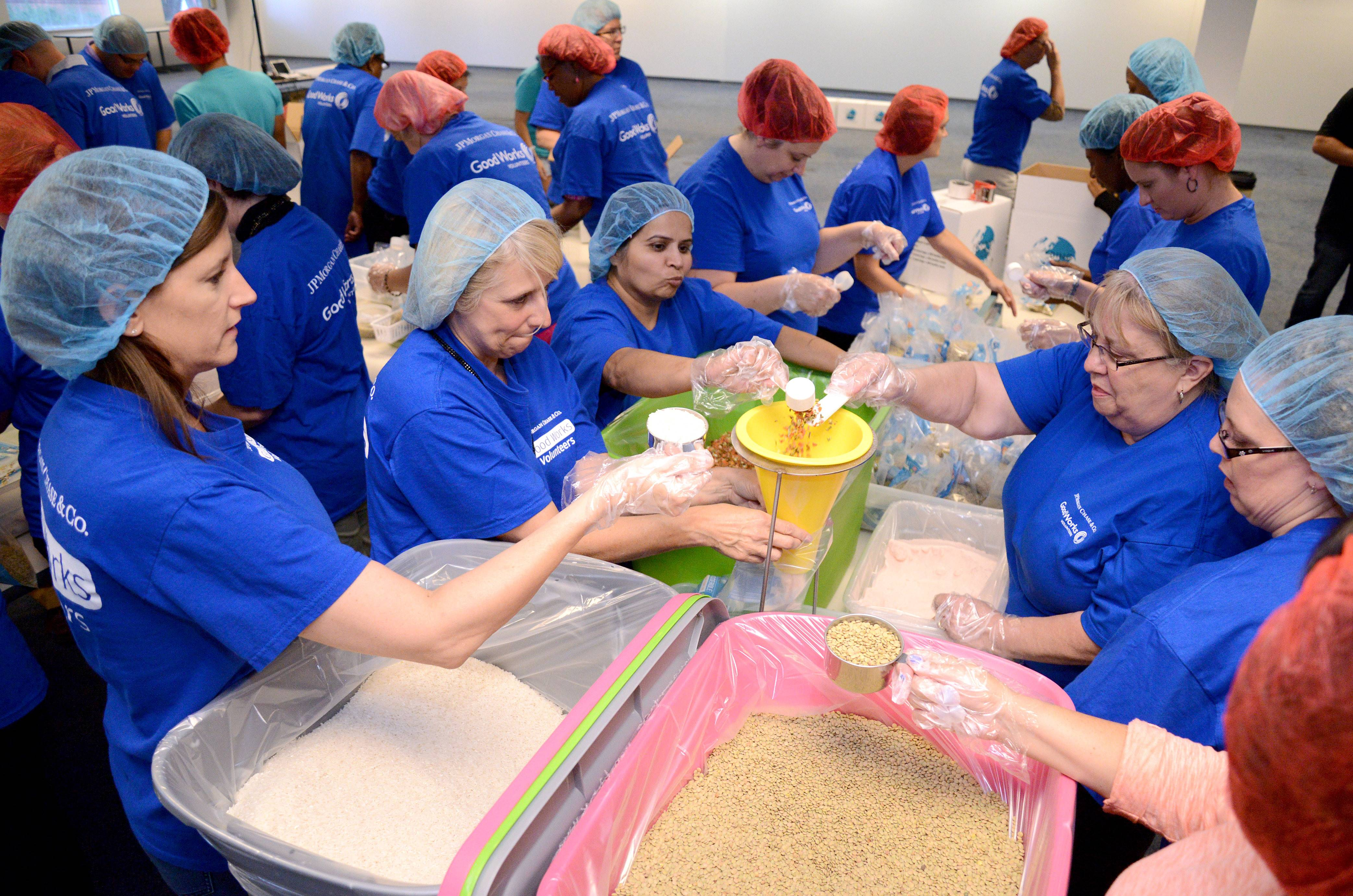 Volunteers at Chase's Elgin facility team up to package 12,000 meals within the first hour of the company event Thursday.