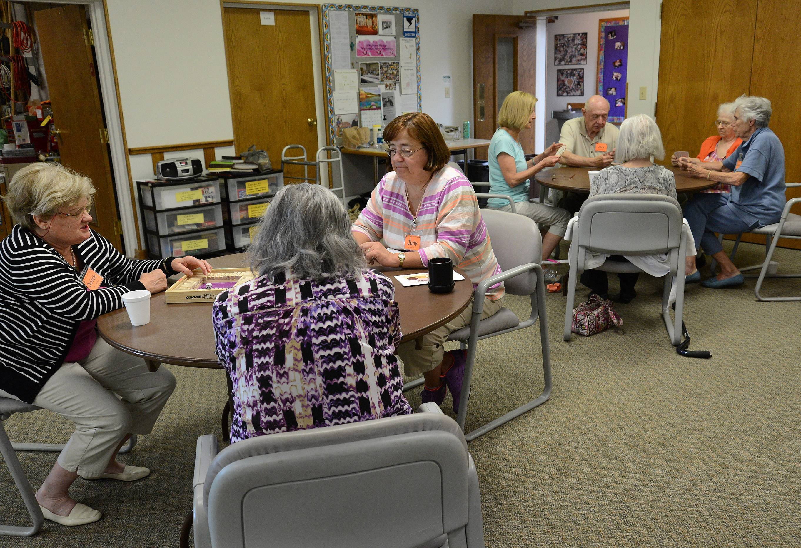 Volunteers and guests play cards at A Caring Place in Elk Grove Village.