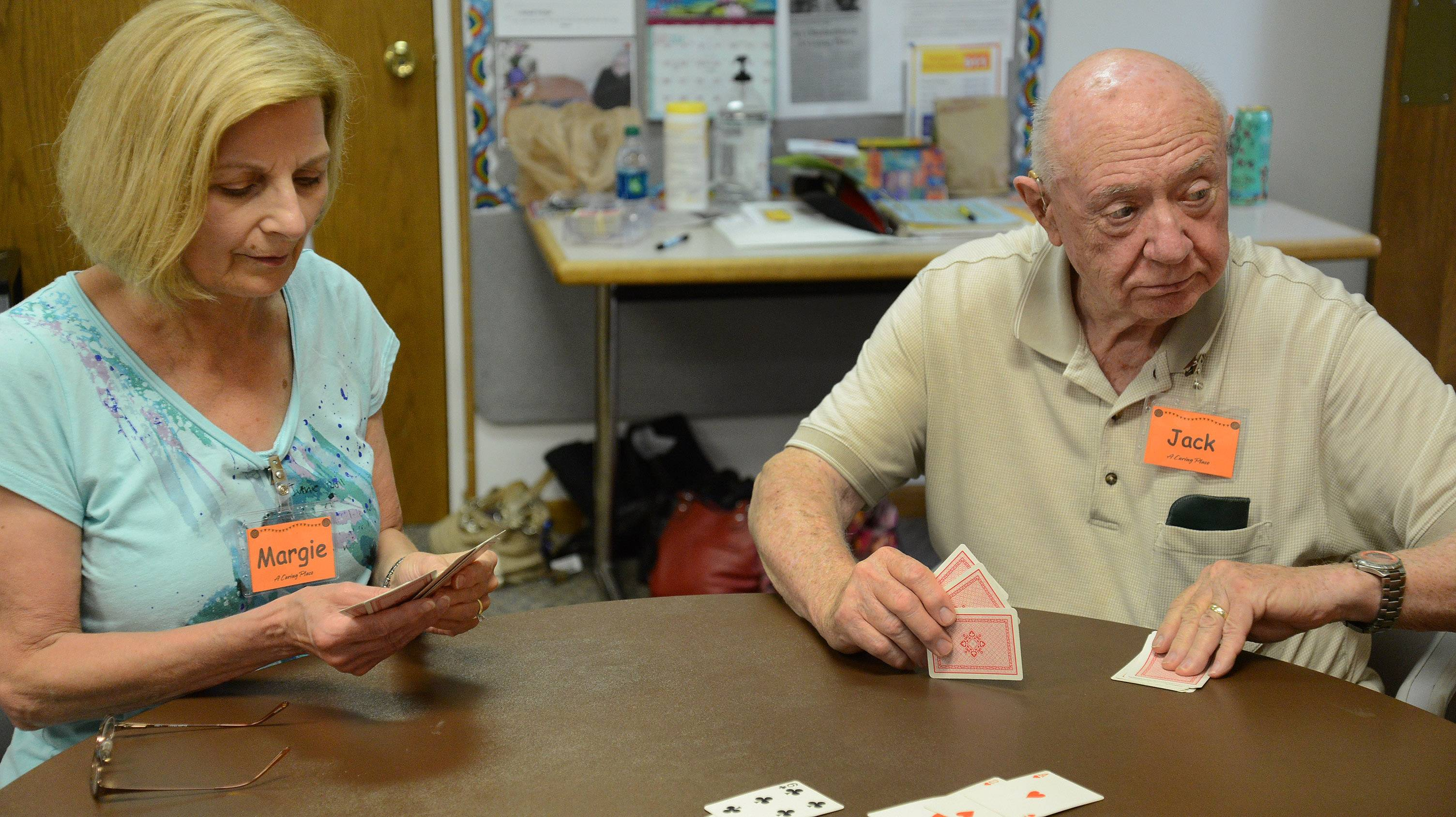 Jack Ryan prepares to deal, alongside volunteer Margie Ewart on a recent Monday at A Caring Place.