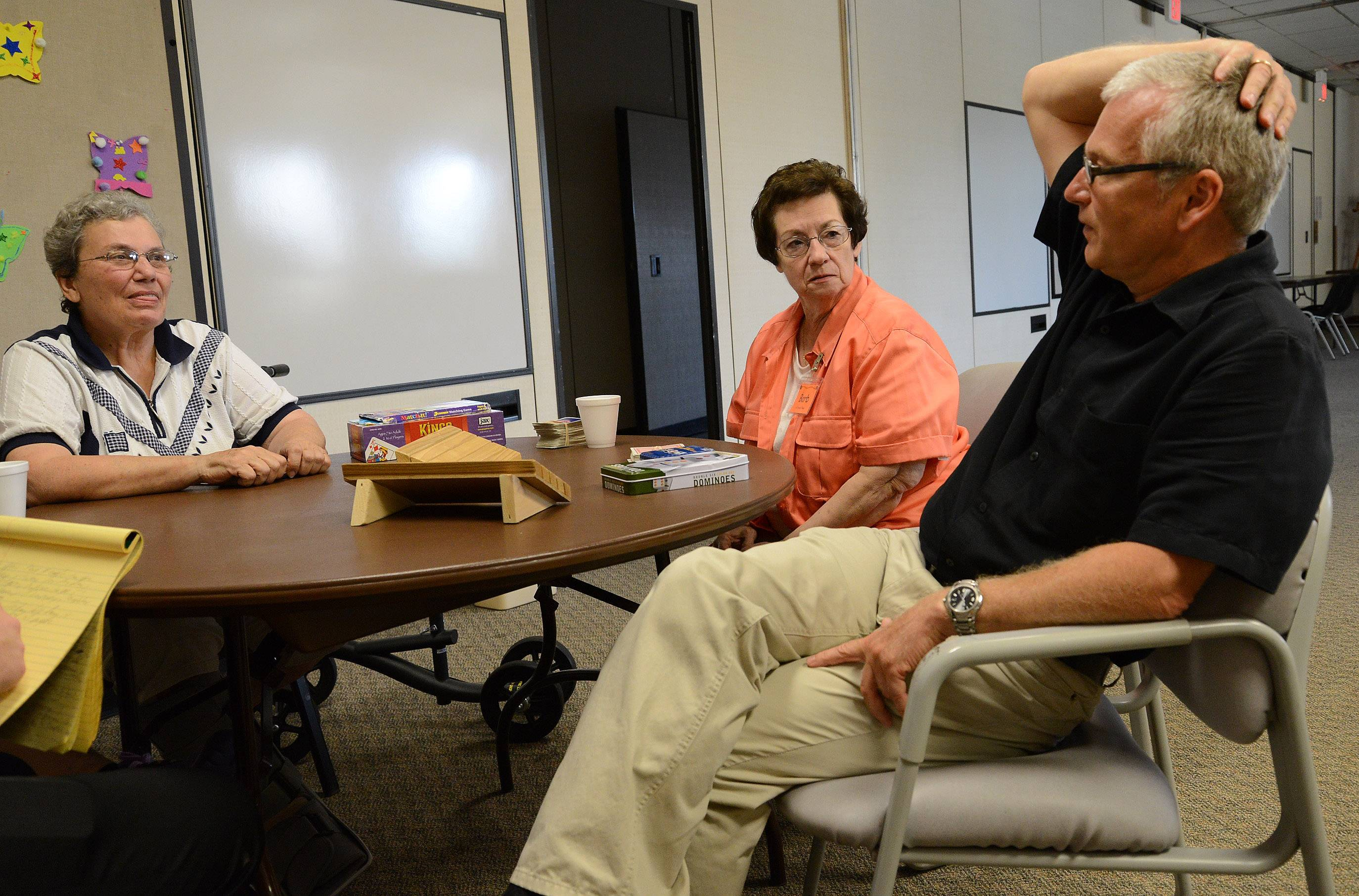 Co-coordinators Marge Hart, left, and Barb Walker talk with Pastor Stefen Potuznik of Christus Victor Lutheran Church at A Caring Place.