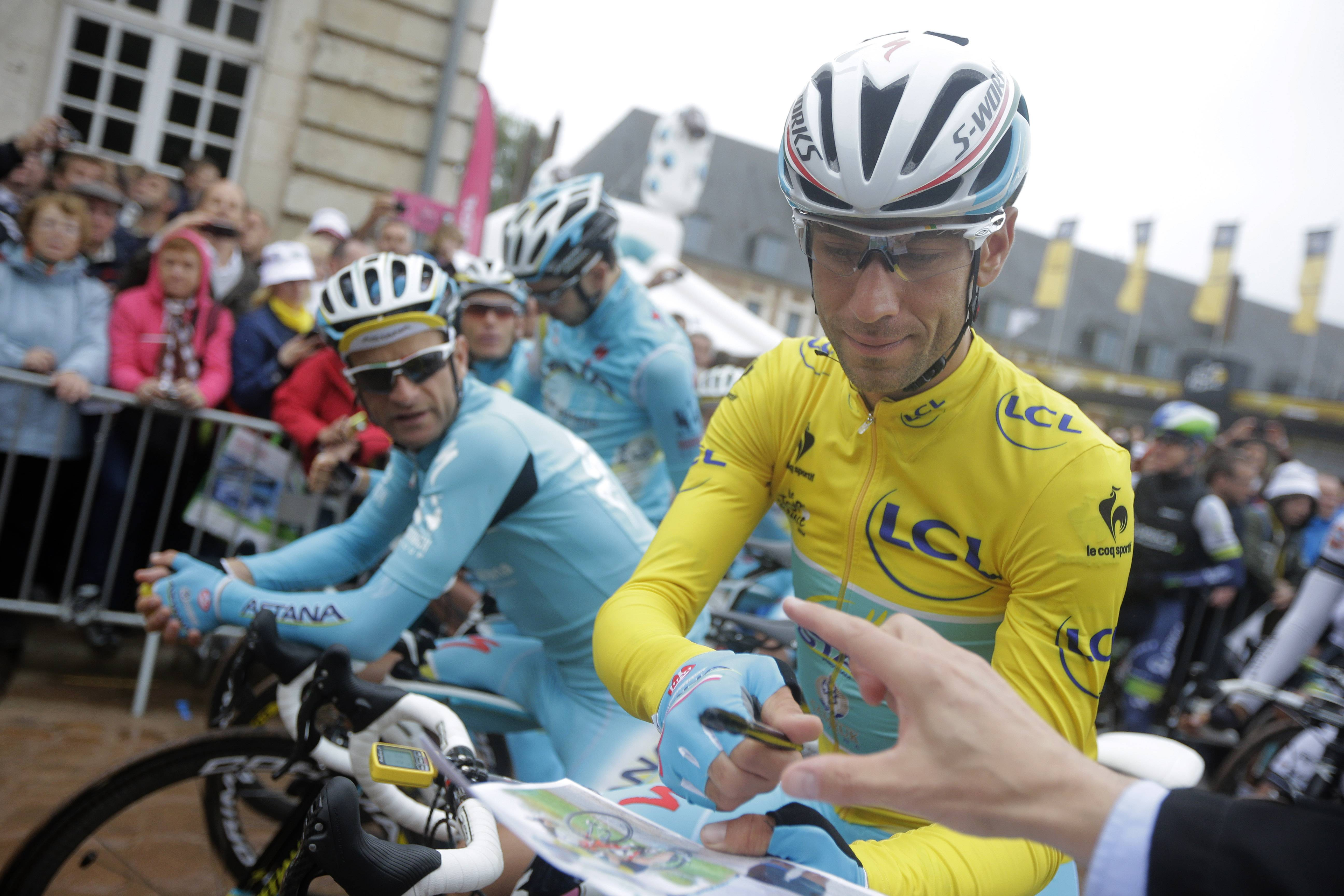 Italy's Vincenzo Nibali, wearing the overall leader's yellow jersey, signs autographs prior to the start of the sixth stage of the Tour de France cycling race over 194 kilometers (120.5 miles) with start in Arras and finish in Reims, France, Thursday.