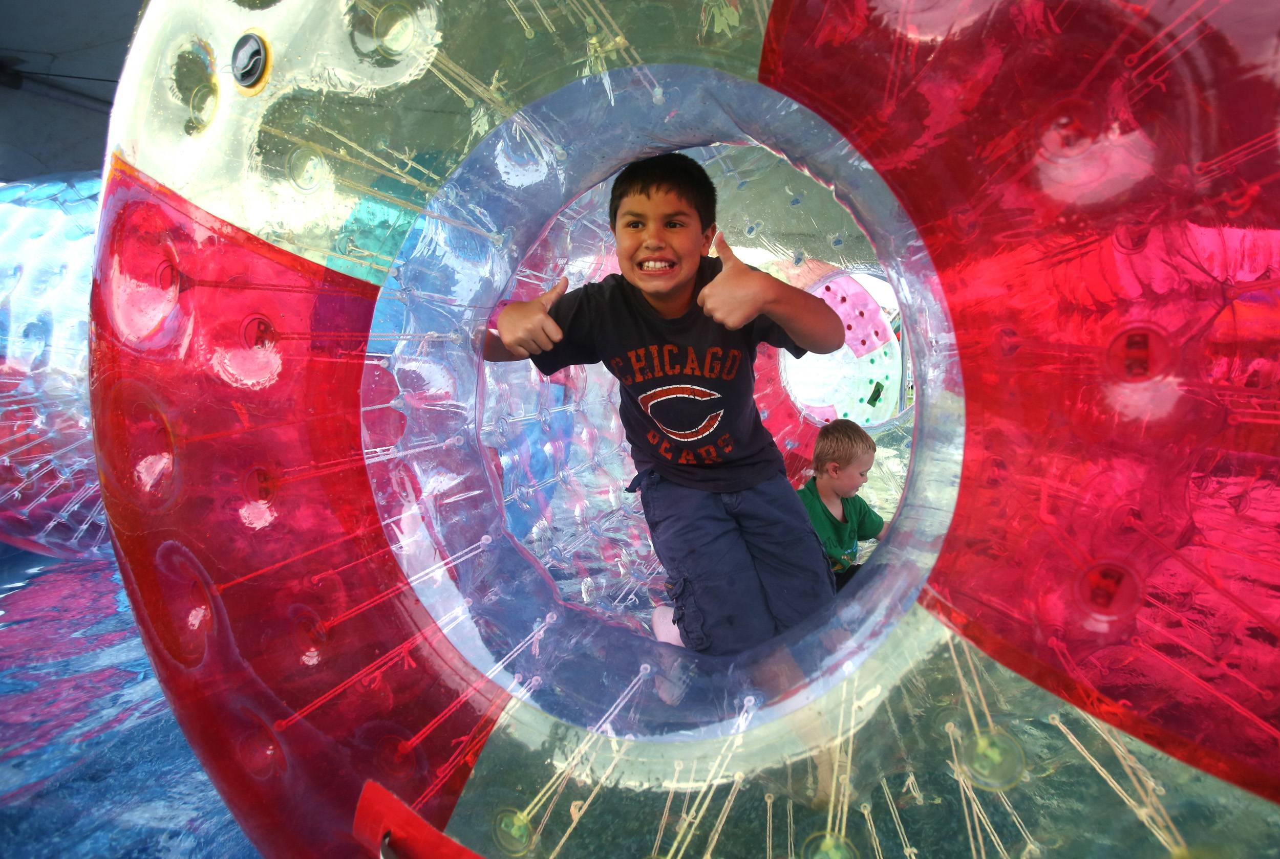 Daniel White/dwhite@dailyherald.com Sam Casas, 10, of Glen Ellyn gives the thumbs-up on a Hamster Roller water wheel during Glendale Heights Fest in Camera Park. Matthew Beach, 5, of Glen Ellyn sits down in the back of the roller.