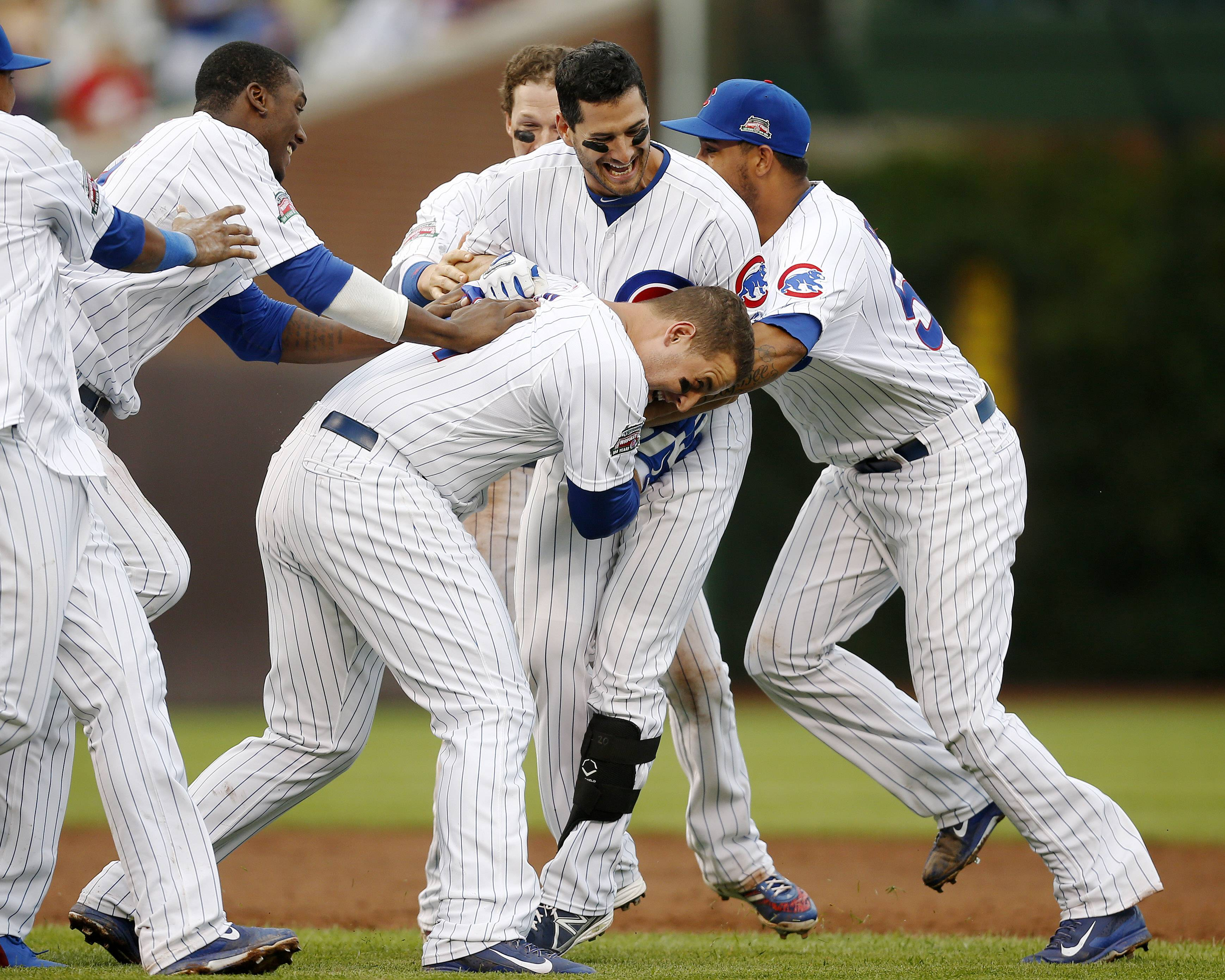 Cubs pile onto Justin Ruggiano, center, after Ruggiano hit a game winning RBI single against the Atlanta Braves during the ninth inning of a baseball game on Friday. The Cubs won 5-4.