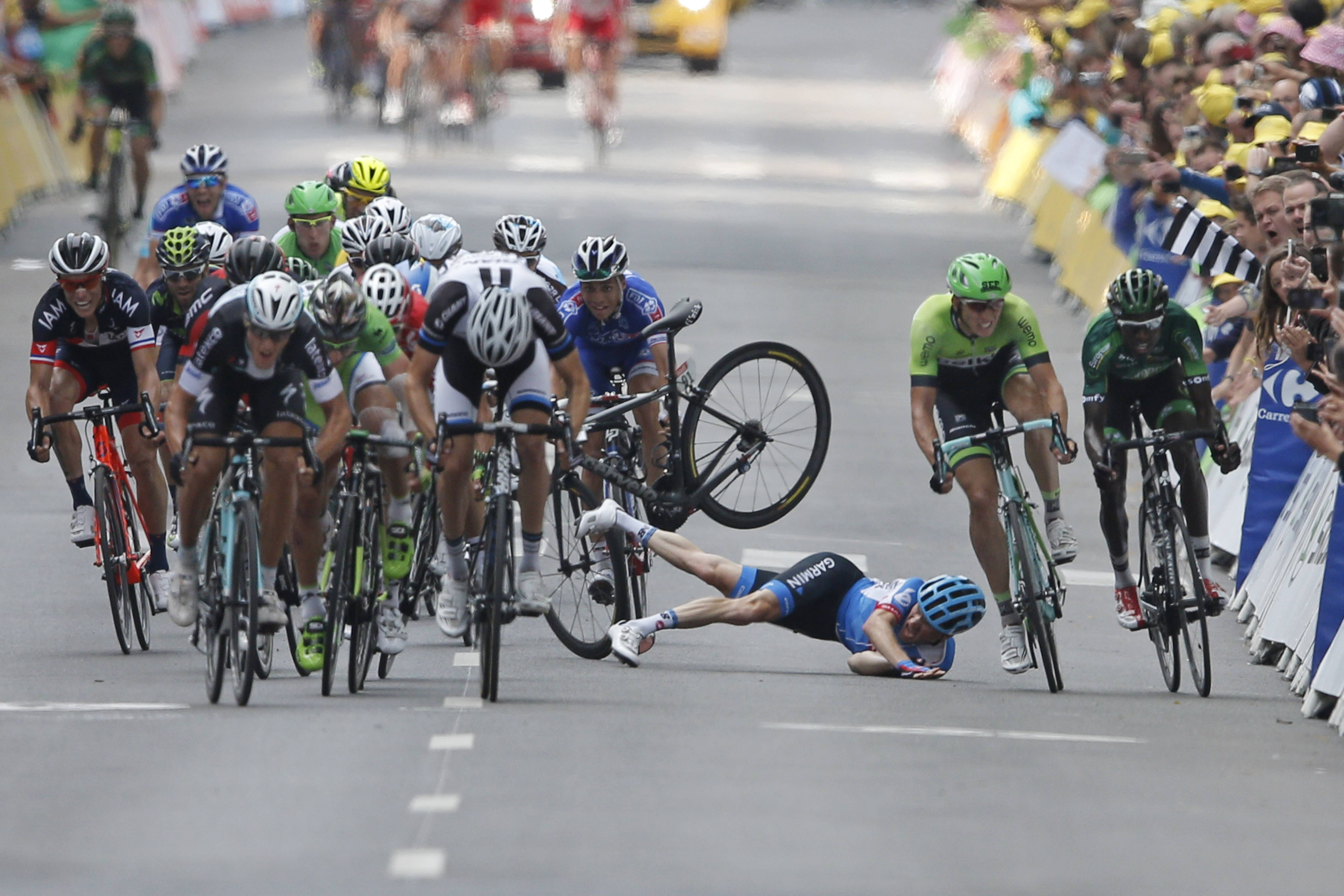 Andrew Talansky of the U.S. crashes as the pack with stage winner Italy's Matteo Trentin, foreground left, sprints towards the finish line during the seventh stage of the Tour de France cycling race over 234.5 kilometers (145.7 miles) with start in Epernay and finish in Nancy, France, Friday, July 11, 2014. (AP Photo/Peter Dejong)