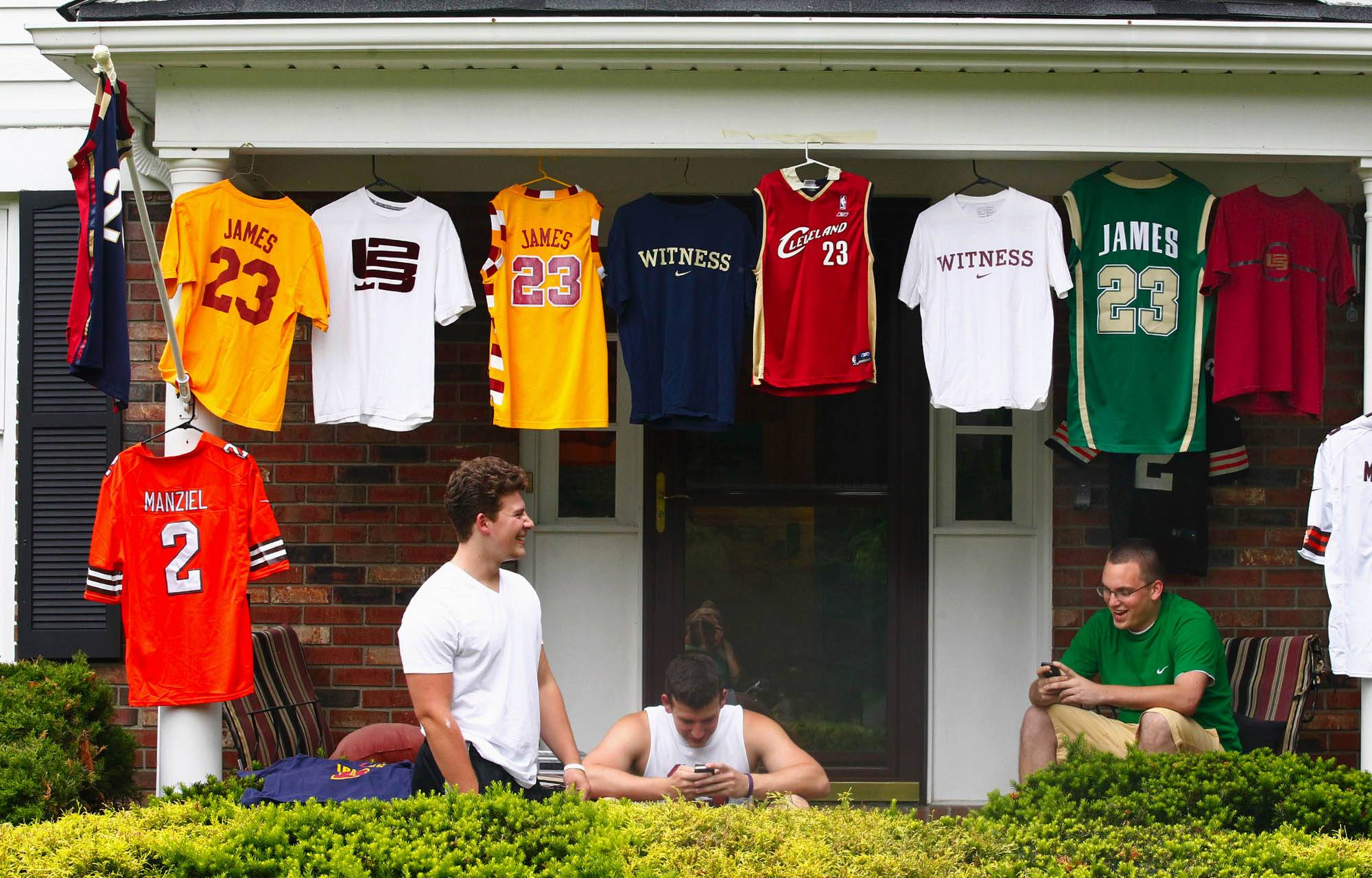 Joe D'Amico, left, his brother Billy D'Amico, center, and their friend Josh Heckman, await the news of where LeBron James will play basketball next year under their LeBron James gear as they watch the fans and media gather in front of the home of LeBron James on Thursday, July 10, 2014 in Bath Township, Ohio. The D'Amicos are neighbors of James.