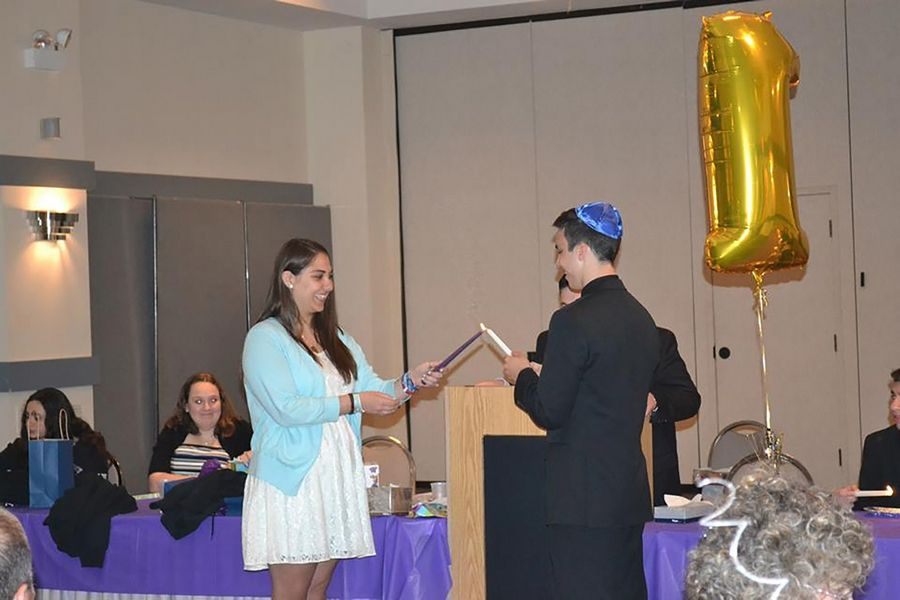 Cara Goldberg, left, passes the presidency of Beth Judea United Synagogue Youth to Joel Spiegel during an installation ceremony.