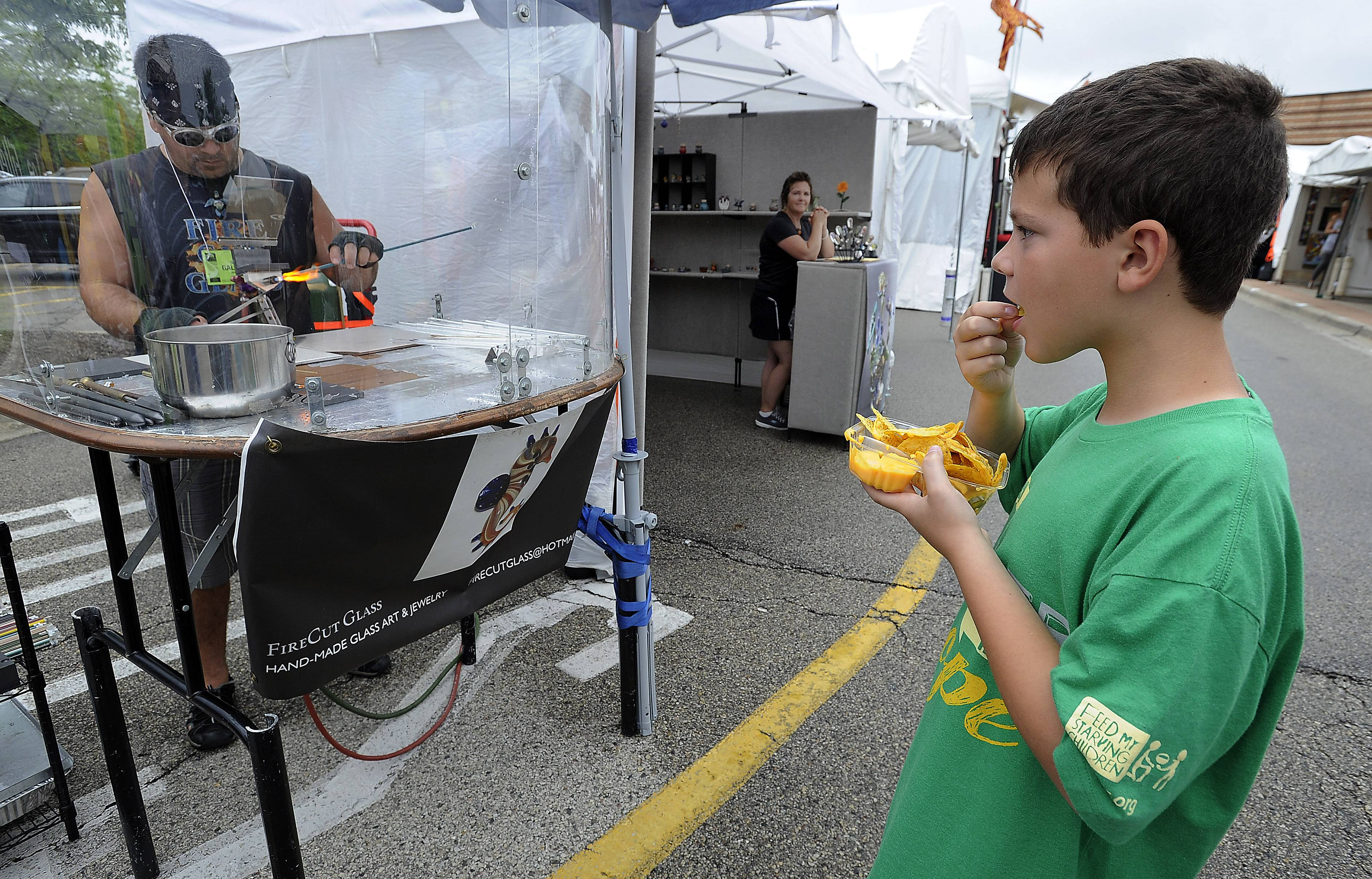 Matthew Scherer, 10, of Arlington Heights enjoys some nachos Saturday at the Buffalo Grove Arts Festival while watching Nick Galatte of Monee shape a piece of glass into a work of art.