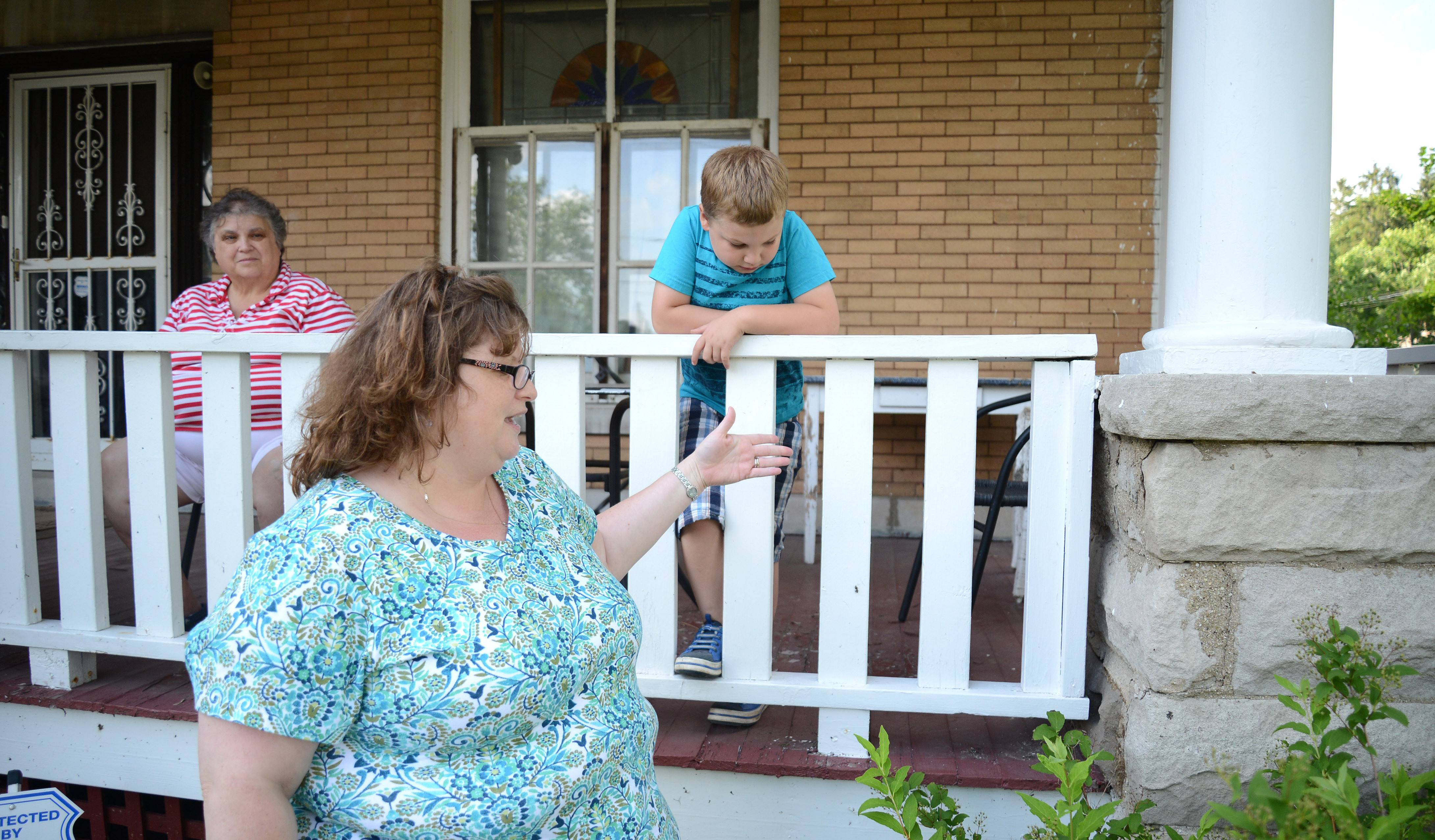 Jennifer Phillips talks about wanting to fix the stone pillars of her family's circa 1916 home. This is the type of project that would be eligible for funding from a new grant program from the group Admirers of Beautiful Old Dwellings of Elgin. Phillips is the group's co-president. Her mother, Anne Bird, of Elgin, and son, Ricky, 6, are on the porch.
