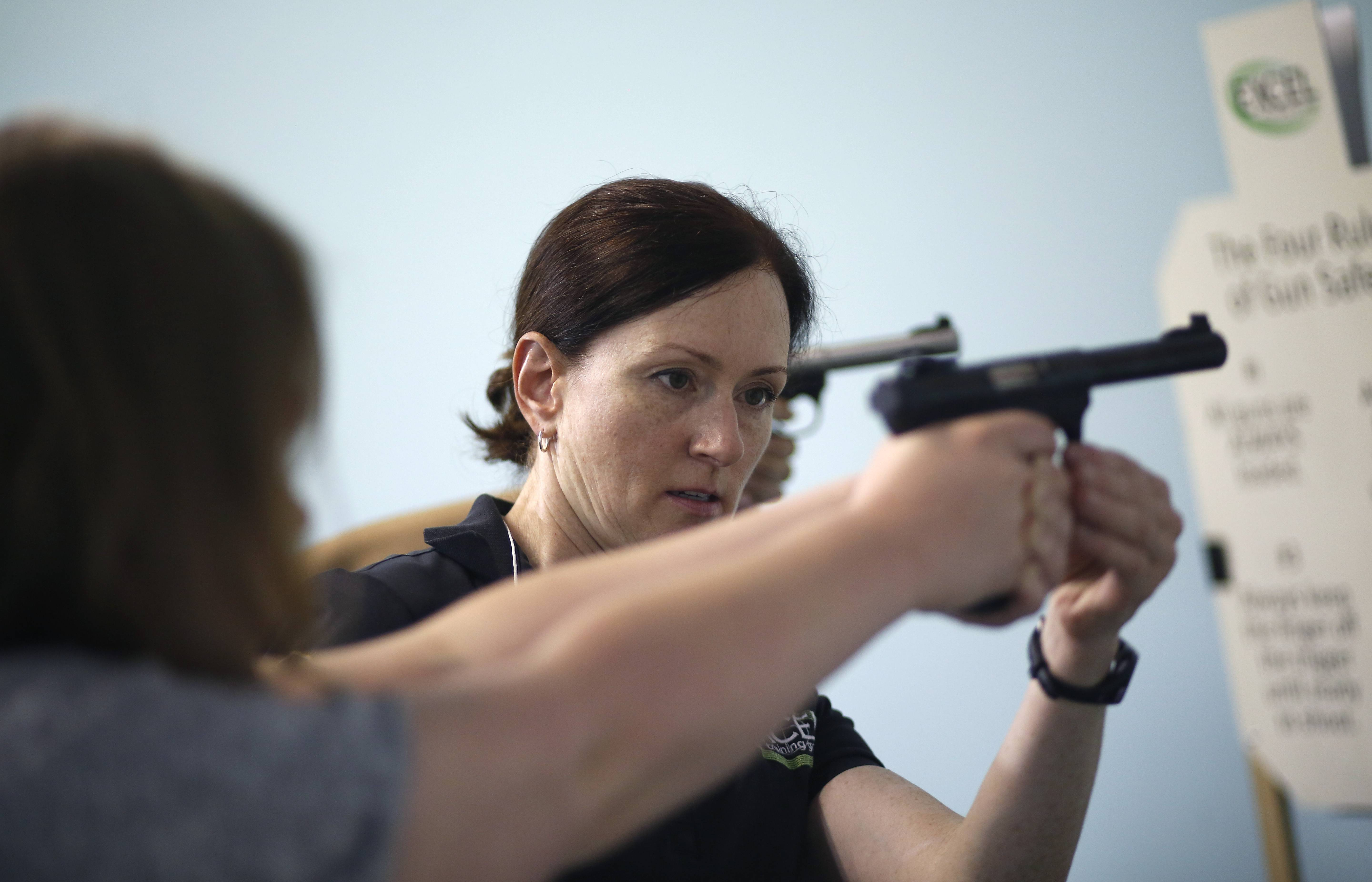 "TD Roe helps adjust a student's grip during a recent class for women. ""When students leave they are much more comfortable handling a firearm,"" she said."