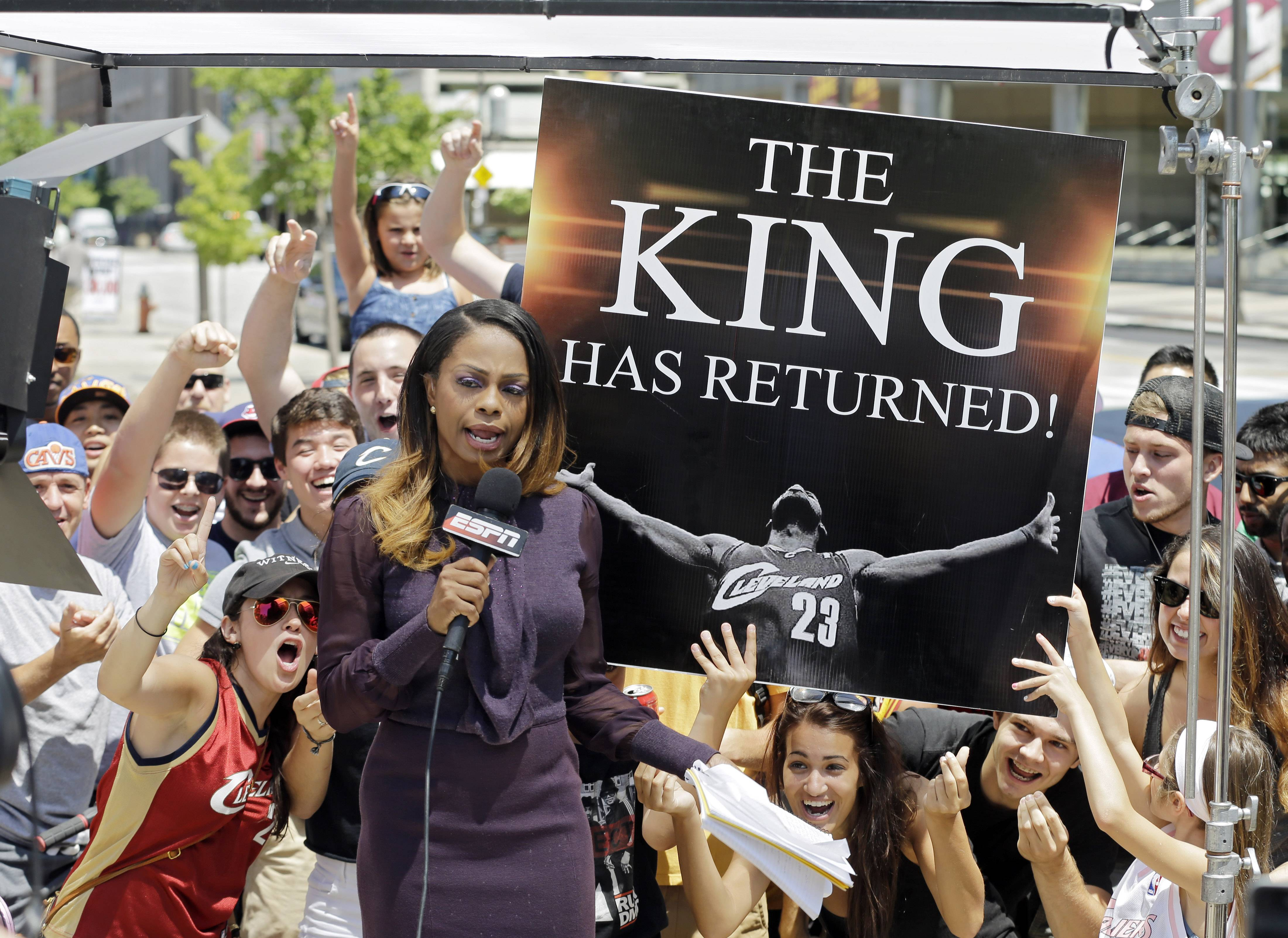 Fans whoop it up behind an ESPN reporter outside Quicken Loans Arena in Cleveland after NBA star LeBron James announced he would return to the Cleveland Cavaliers.