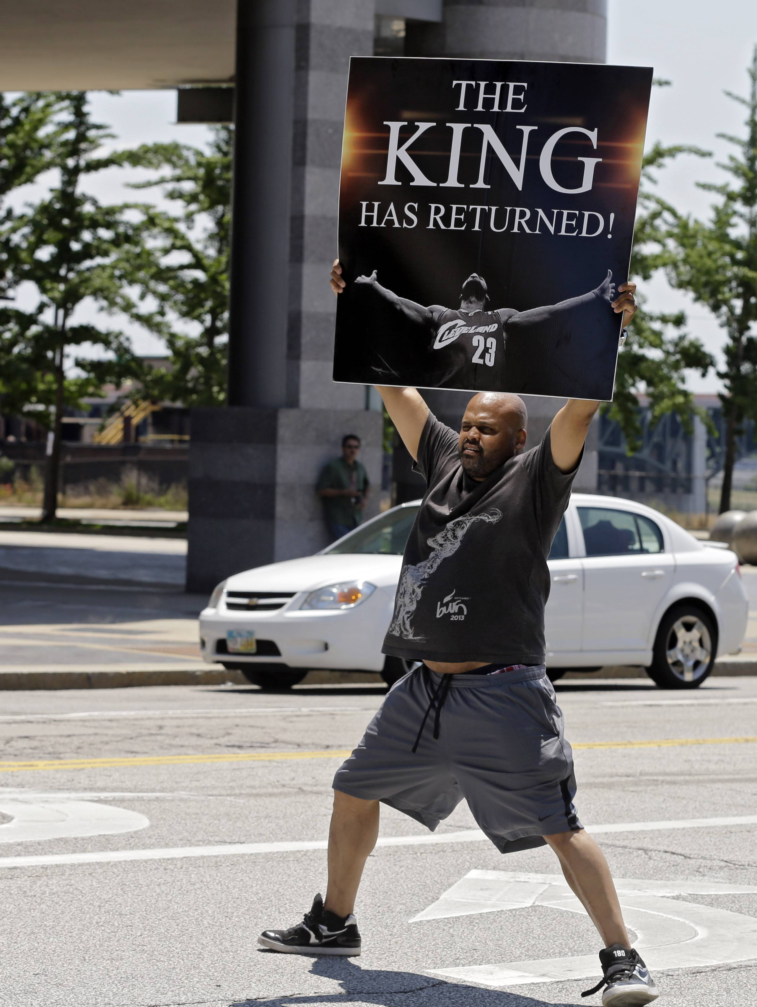 Graphic designer Alvin Smith holds a poster in the street outside Quicken Loans Arena in Cleveland heralding the return of LeBron James.