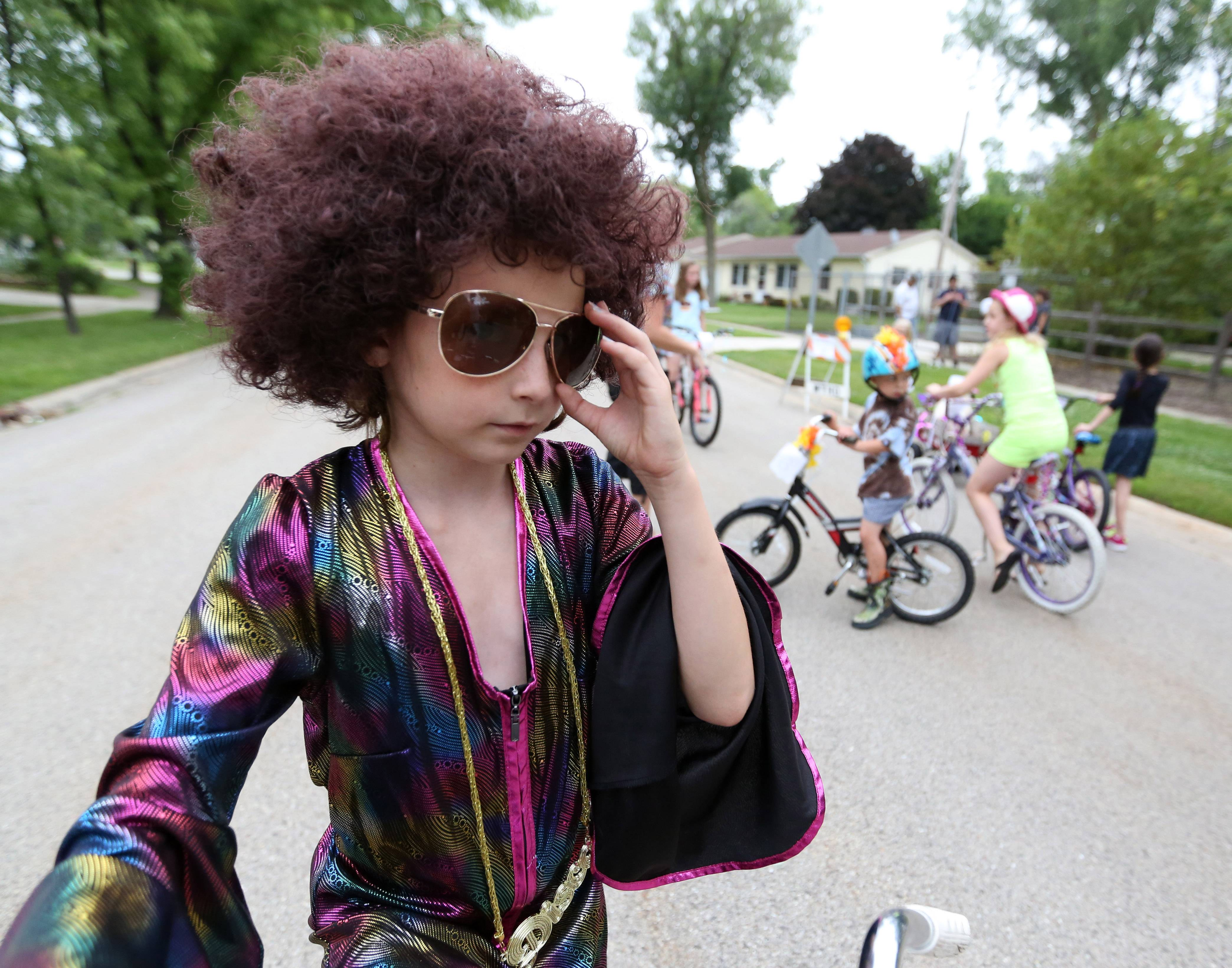 Gia Ruffolo, 8, of Grandwood Park adjusts his cool shades Saturday before leading a judged kids bike parade near Adams Park as part of the Grandwood Park Summerfest.