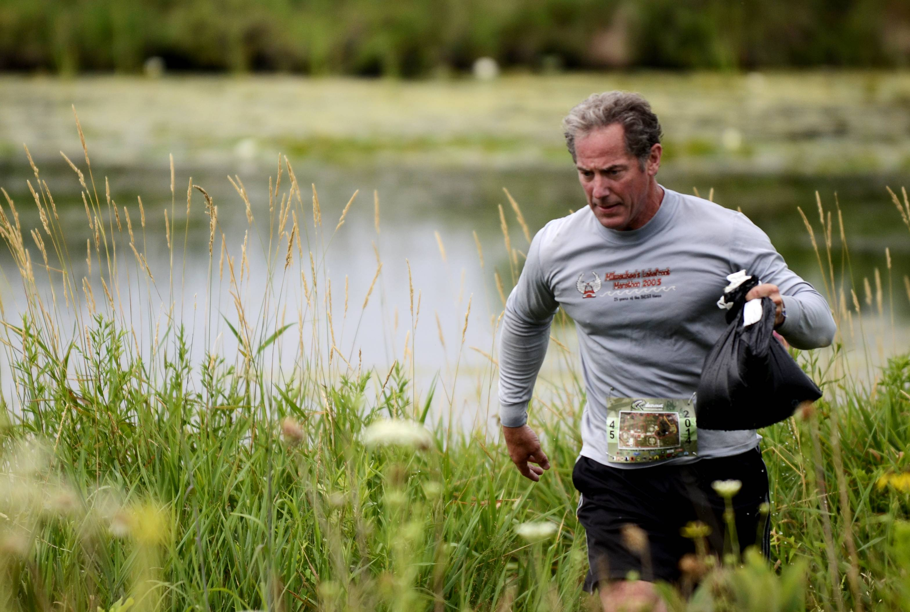 Chris Ivers of Crystal Lake carries a bag of water from the pond to fill a bucket at the RUNdezvous Saturday in Lippold Park in Crystal Lake. Racers must complete 14 skills, such as fire building, hatchet throwing, knot tying and water carrying, during the five-mile event.