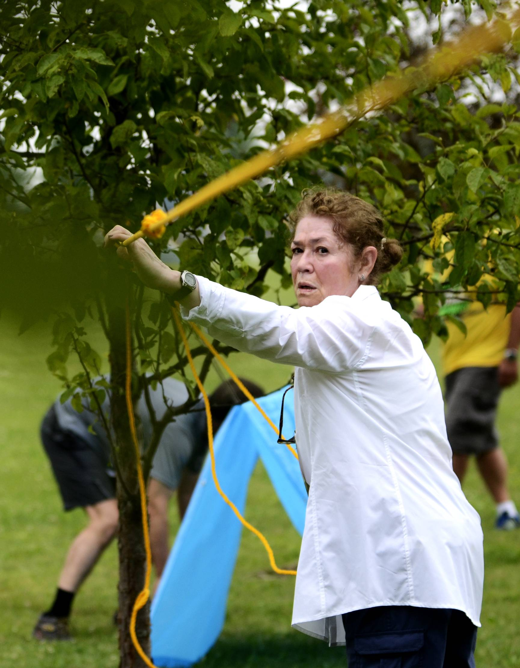 Gloria Kreider of Woodstock secures a rope to make a small shelter Saturday at the RUNdezvous Race in Crystal Lake's Lippold Park.
