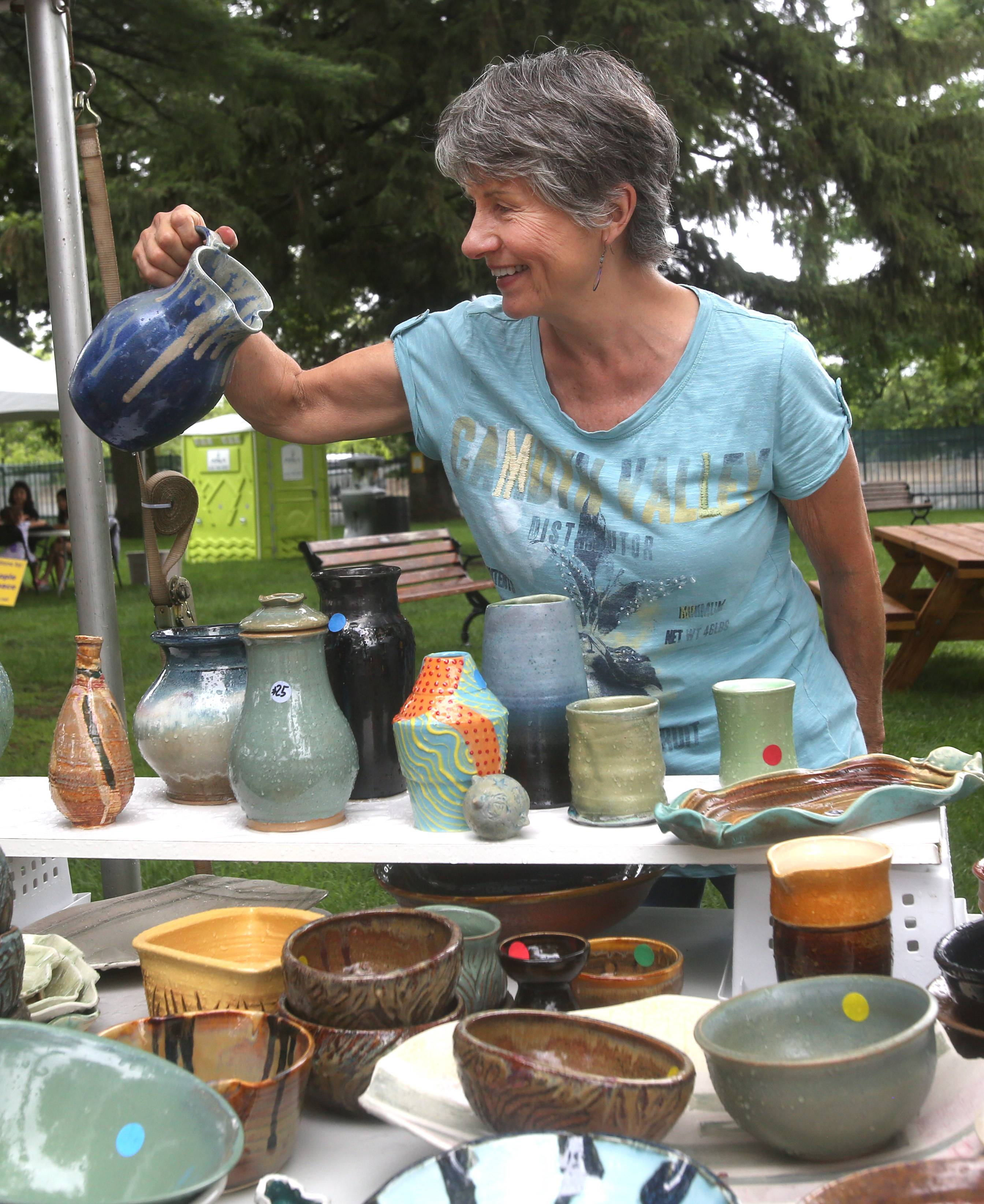 Sue Borghesi, a resident artist at Clay Space Ceramic Arts Studio in Lisle, looks over a pitcher during the Naperville Woman's Club's 55th annual Juried Art Fair at Naper Settlement. All proceeds from the 55 artists in the cooperative at Clay Space Ceramic Arts are donated back to various food pantries throughout the Western suburban communities.